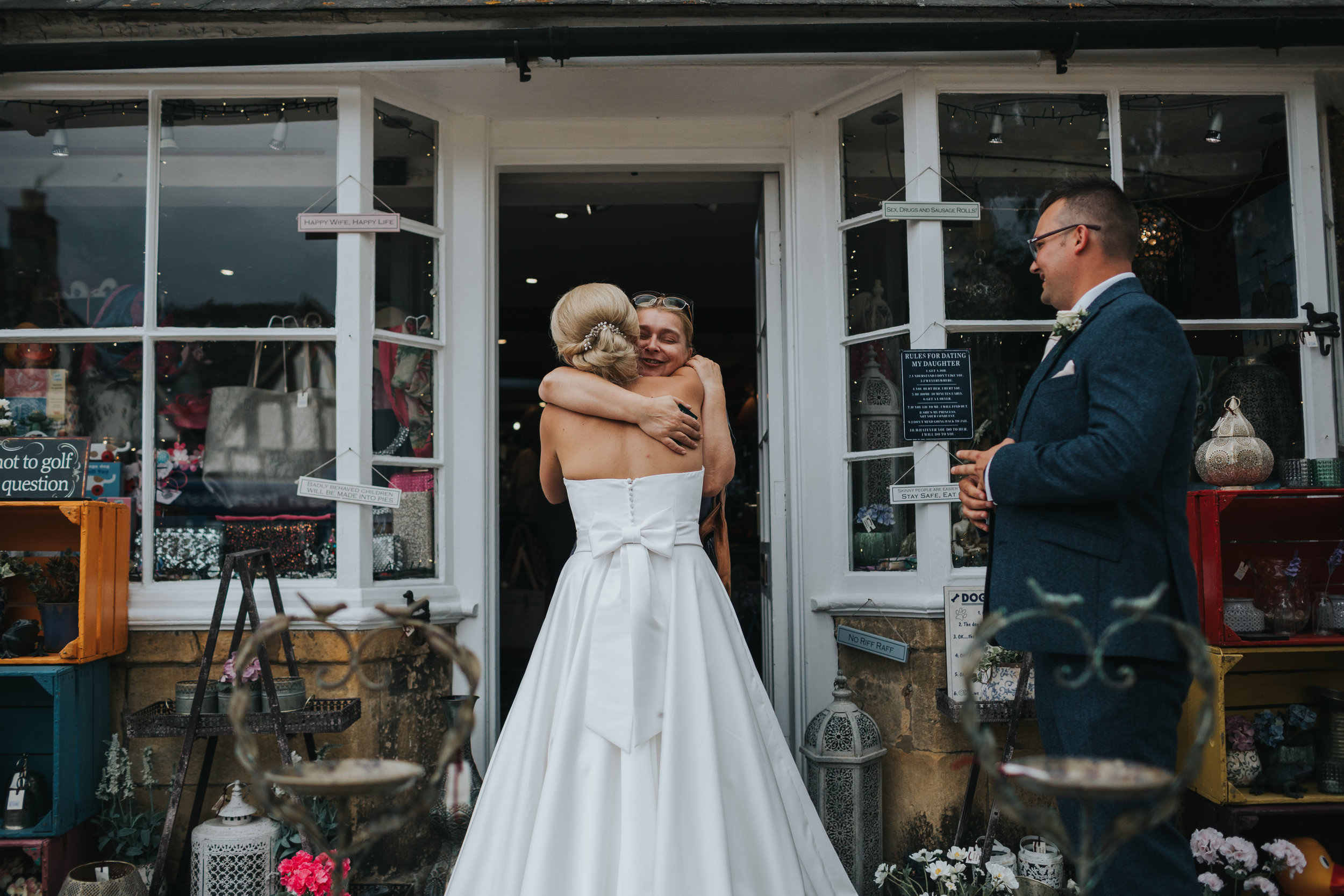 Bride hugs shop keeper.