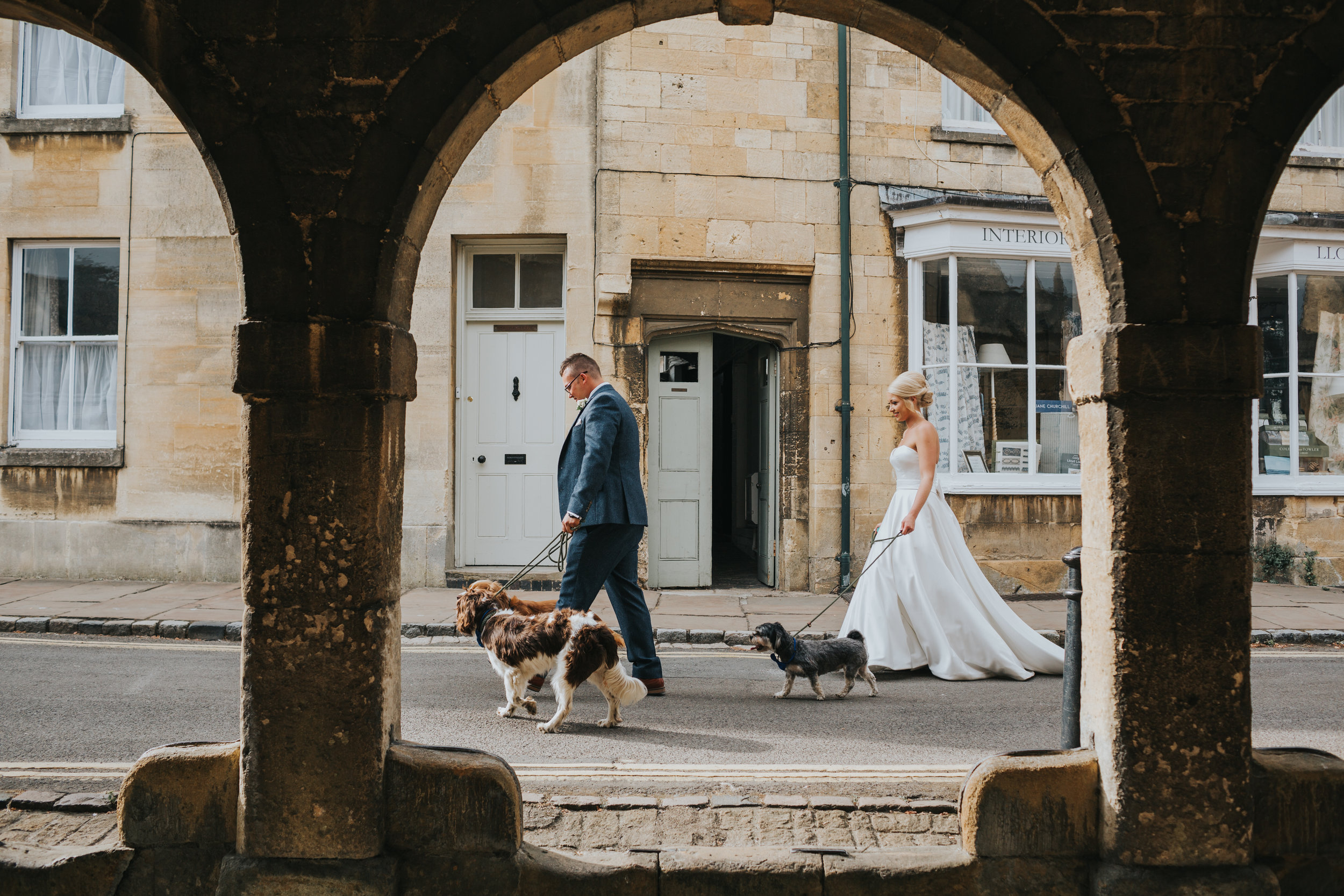 Bride and Groom walk their dogs under arches.
