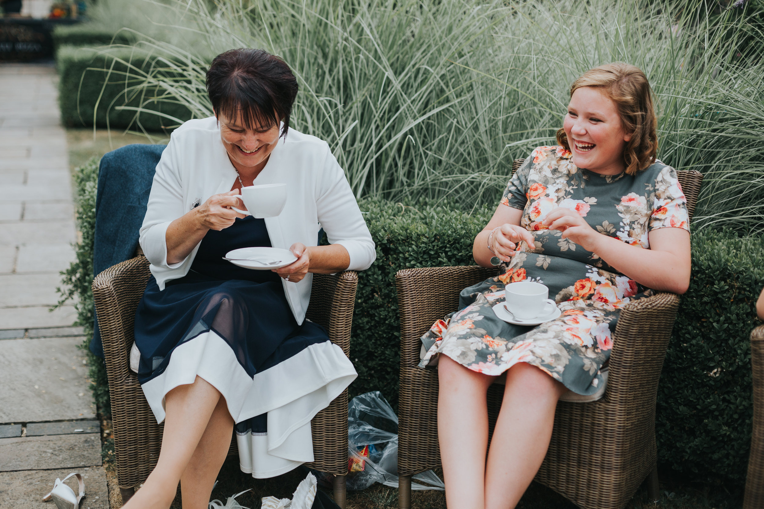 Two female guests laughing together while drinking a cup of tea.