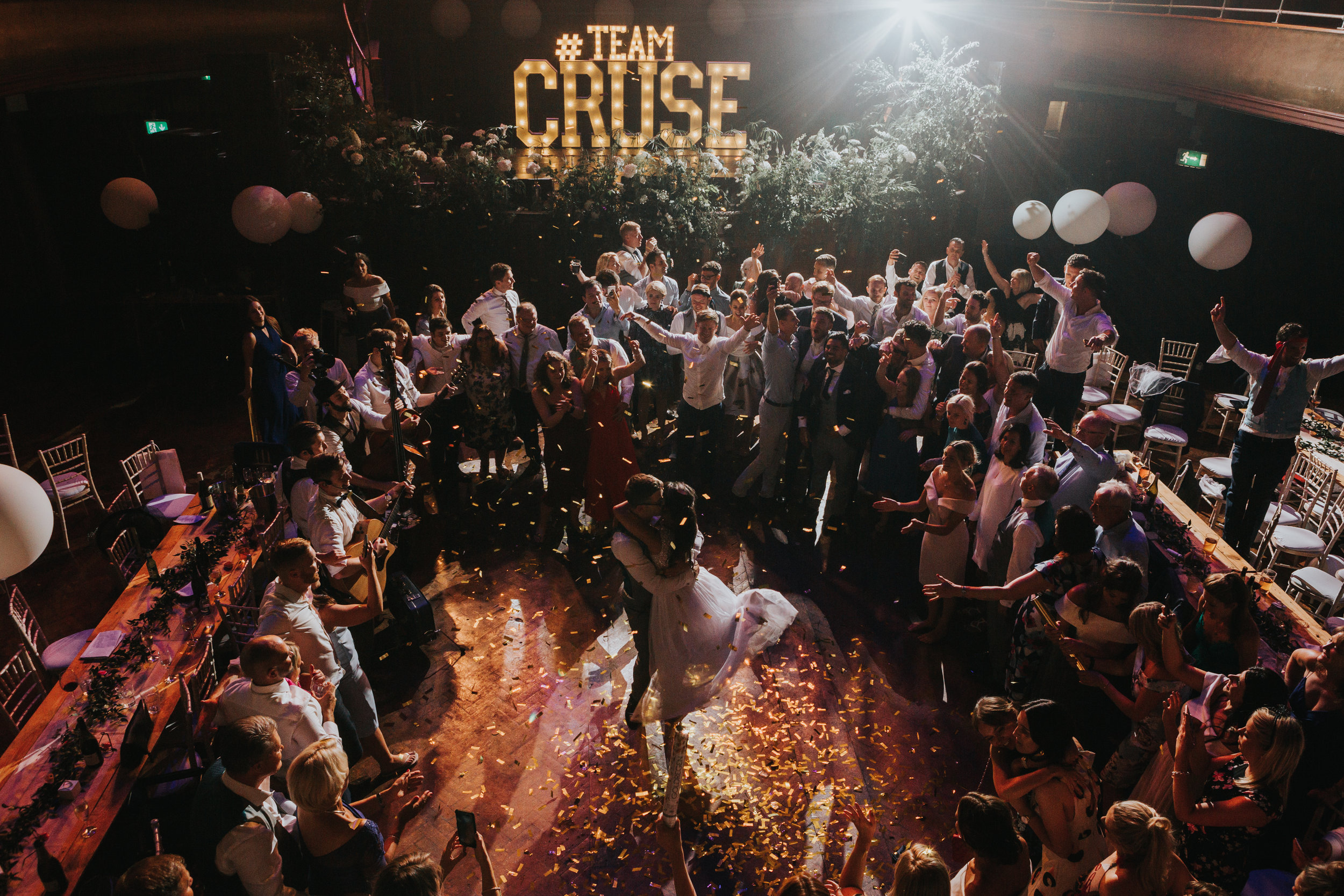 Bride and Groom dance together surrounded by their friends and family as a golden confetti floats down onto them, with the words #TEAMCRUSE in lights behind them. At the Albert Hall Manchester.