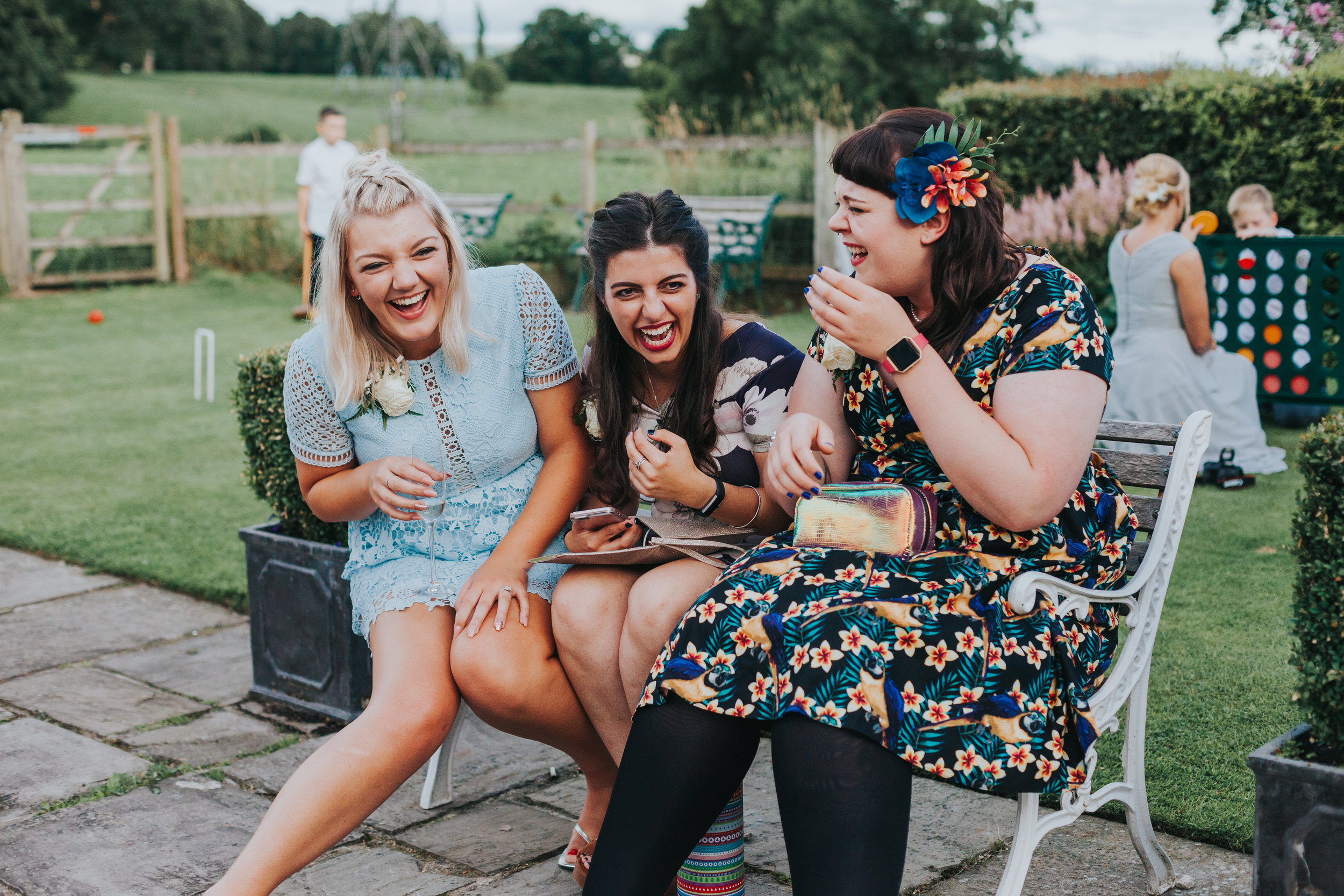 Candid shot of 3 female wedding guests dressed in brightly coloured clothes sit on a bench and laugh together at a wedding in Manchester, while children play lawn games behind them.