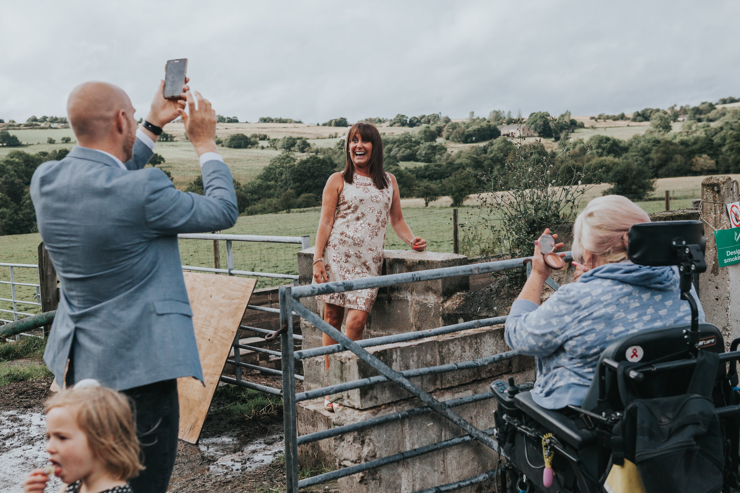 A typical documentary wedding photograph of a guest posing for a photograph taken by her friends phone, while a lady in a wheel chair puts on make up and a little girl walks past eating crisps.