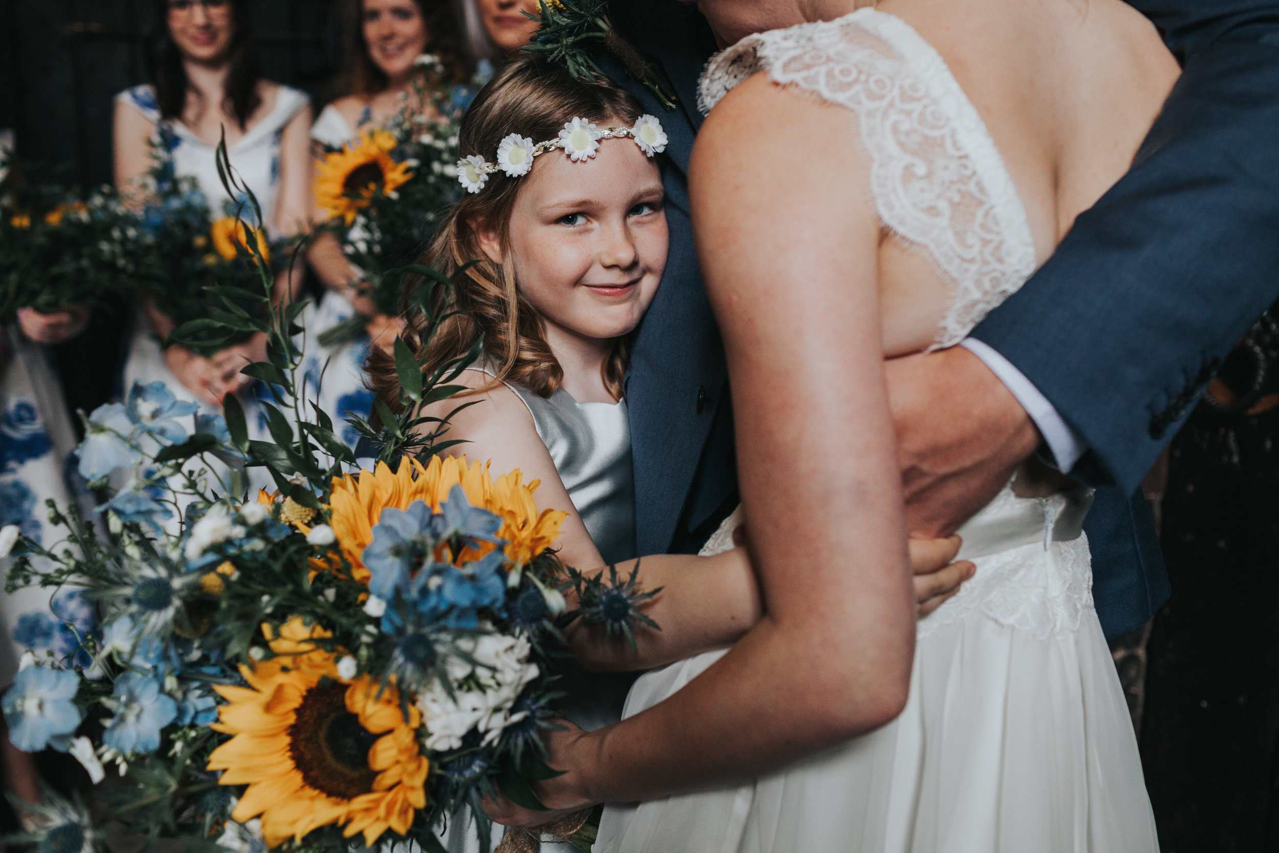 Unposed photograph of a flower girl hugs the bride and groom while looking into the camera at Chetham Library Manchester.