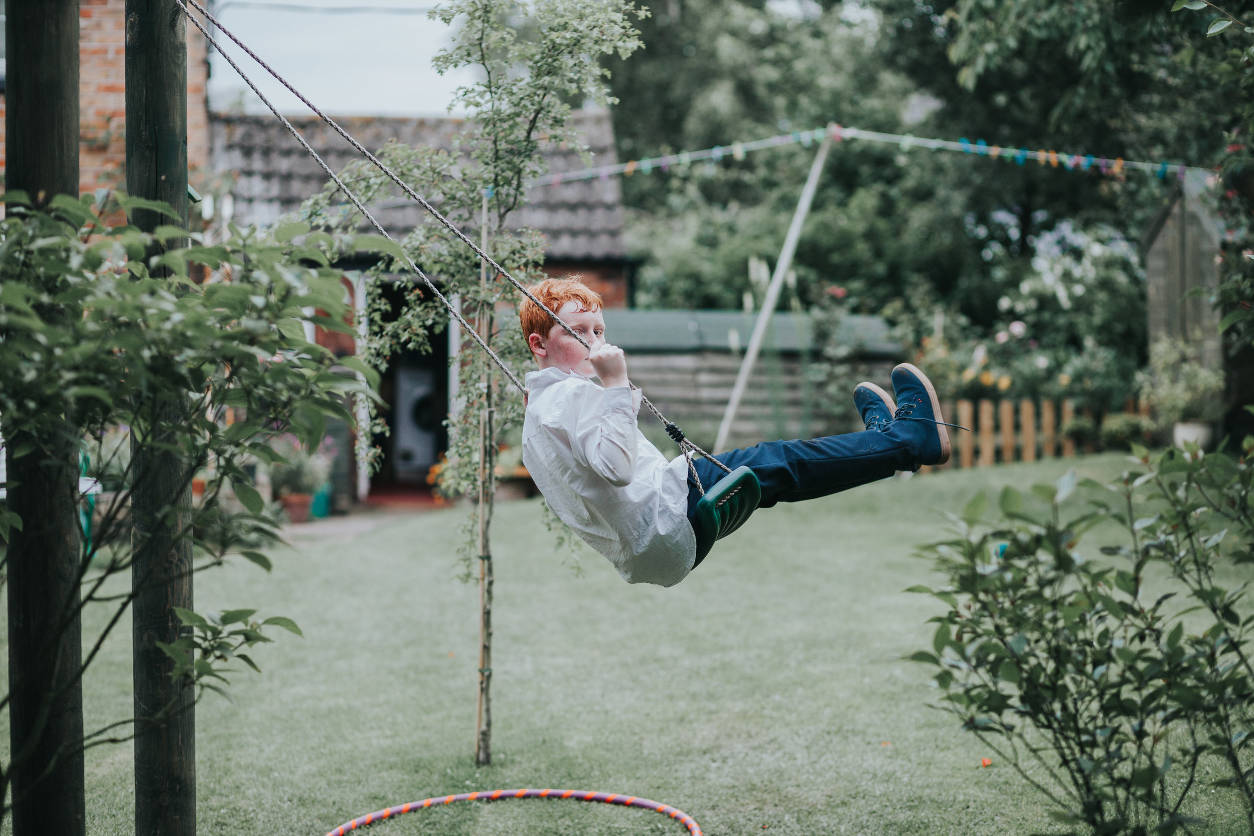 Red haired child catches photographer taking a photo of him at garden party wedding in Manchester.