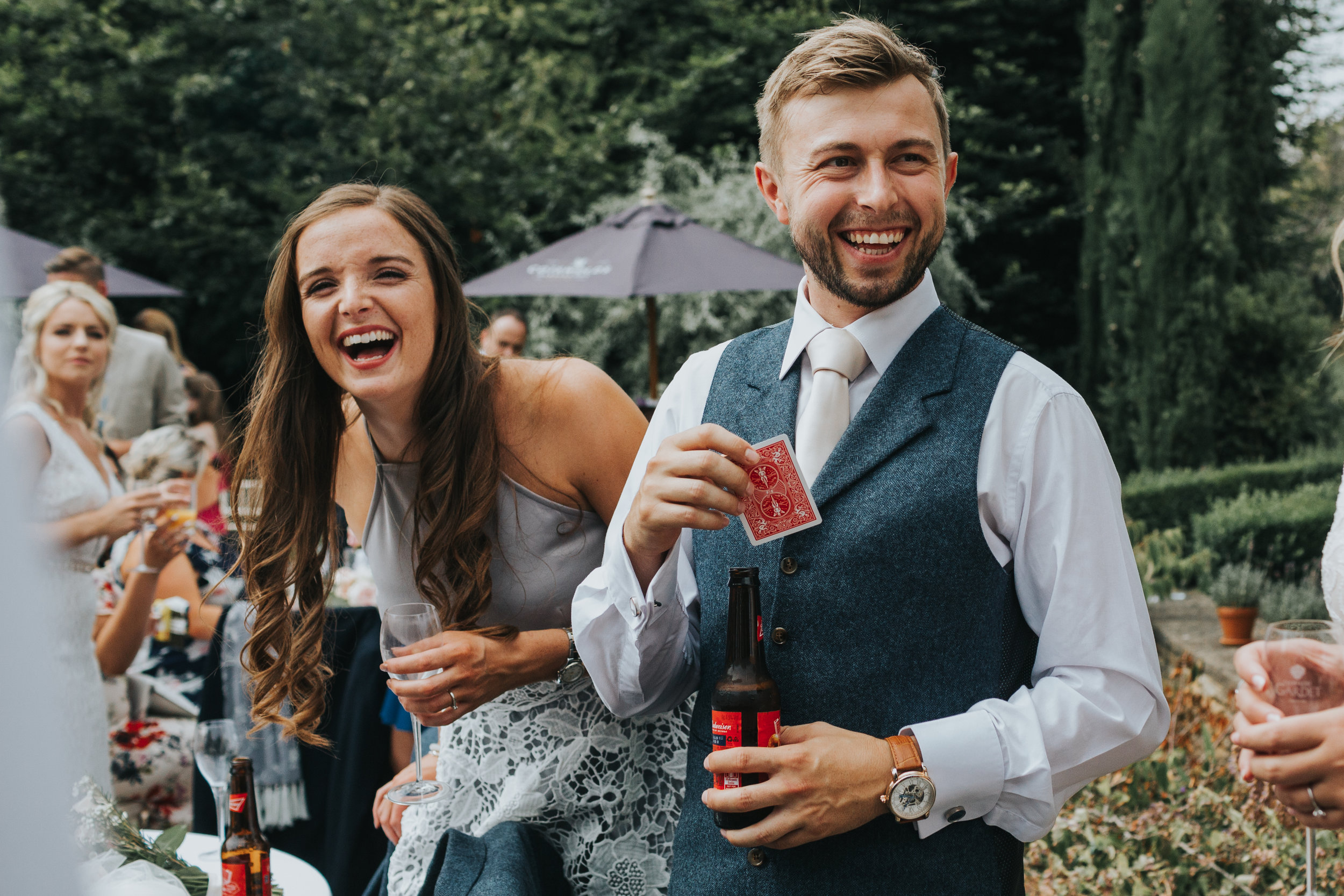 Wedding guests laugh together while playing cards at outdoor wedding, UK.