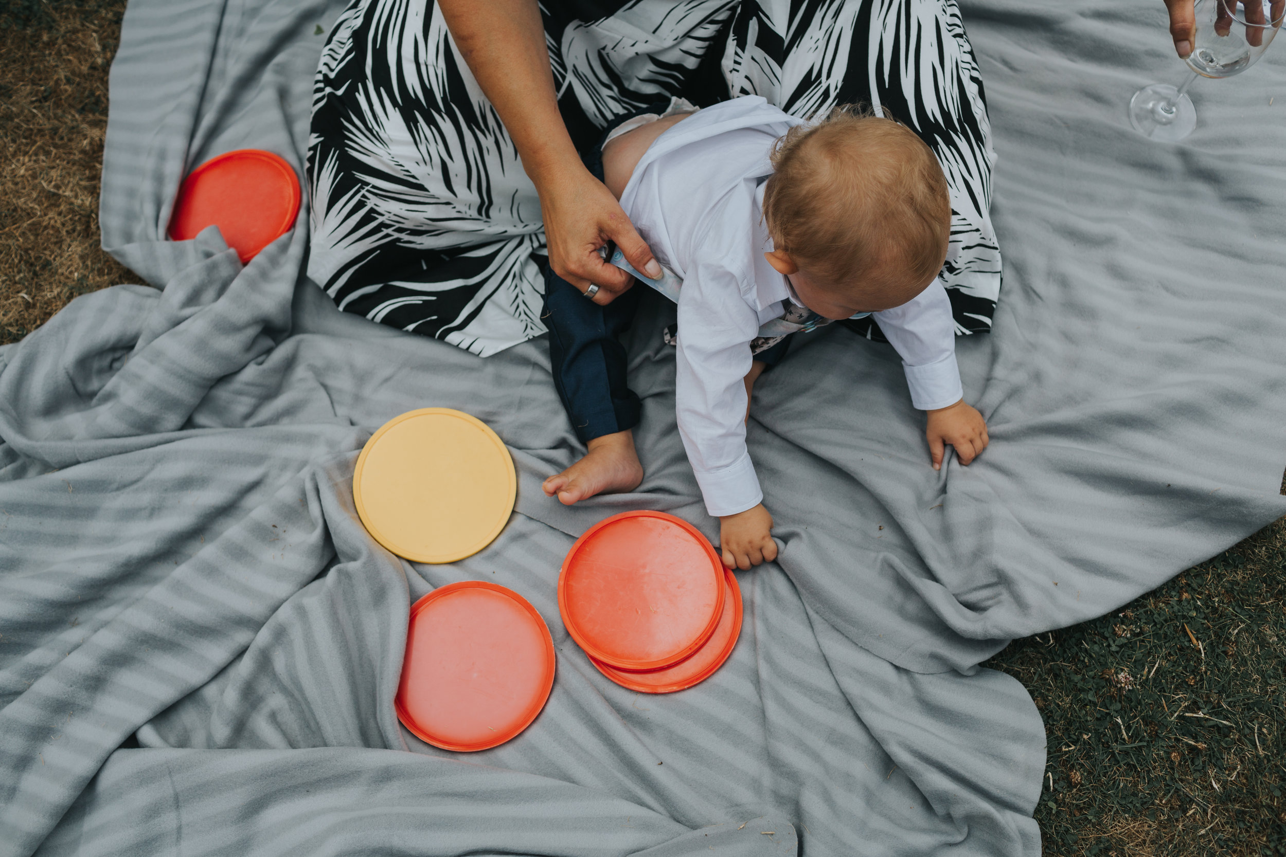 6 month old child photographed from above plays with connect 4 pieces on a grey blanket at an outdoor wedding in Manchester, UK.