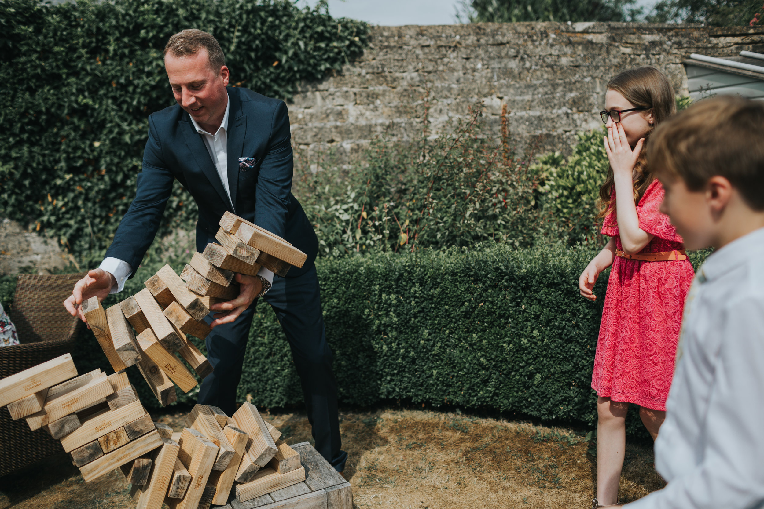 Adult fails at giant jenga at outdoor wedding, while children mock him.