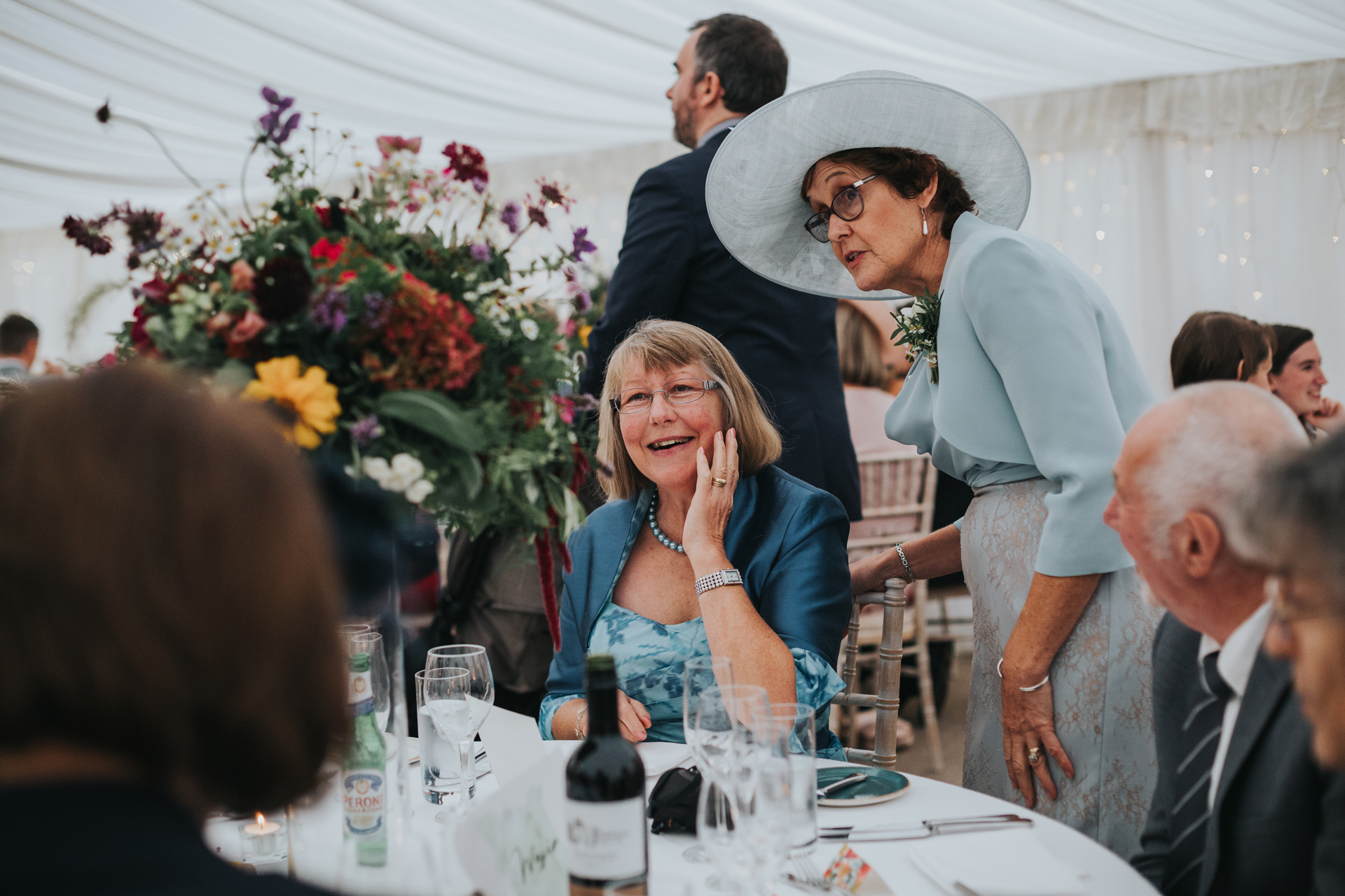 Wedding guests admire the beautiful flowers in the marquee at Goldstone Hall.
