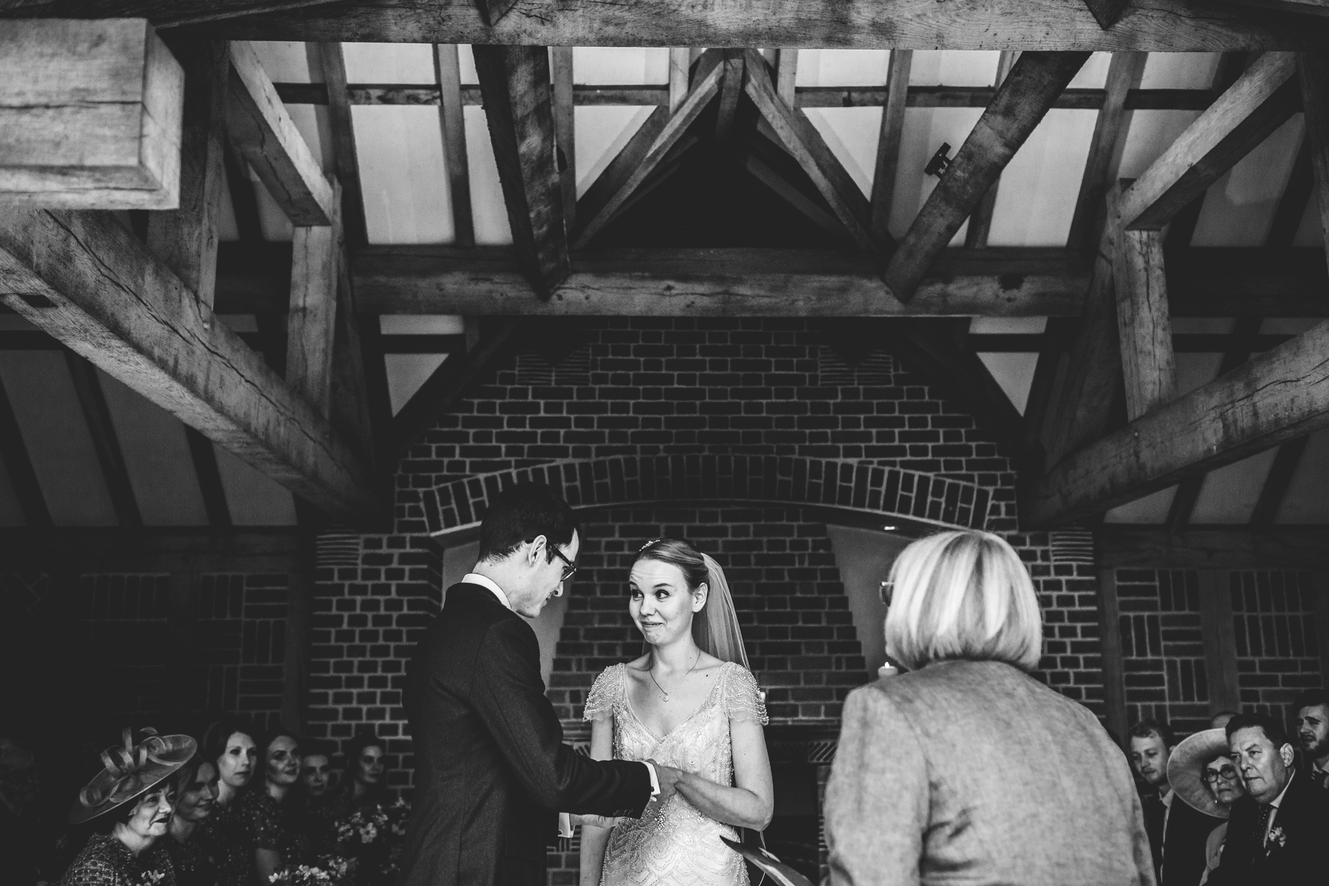 Bride and groom say their vows in an outdoor ceremony at Goldstone Hall, Market Drayton. Photograph in black and white.