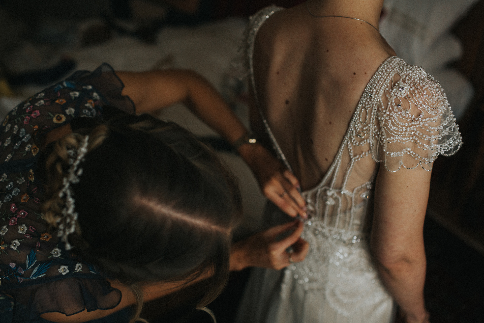 Close up of details of dress as bridesmaid fastens up the back.