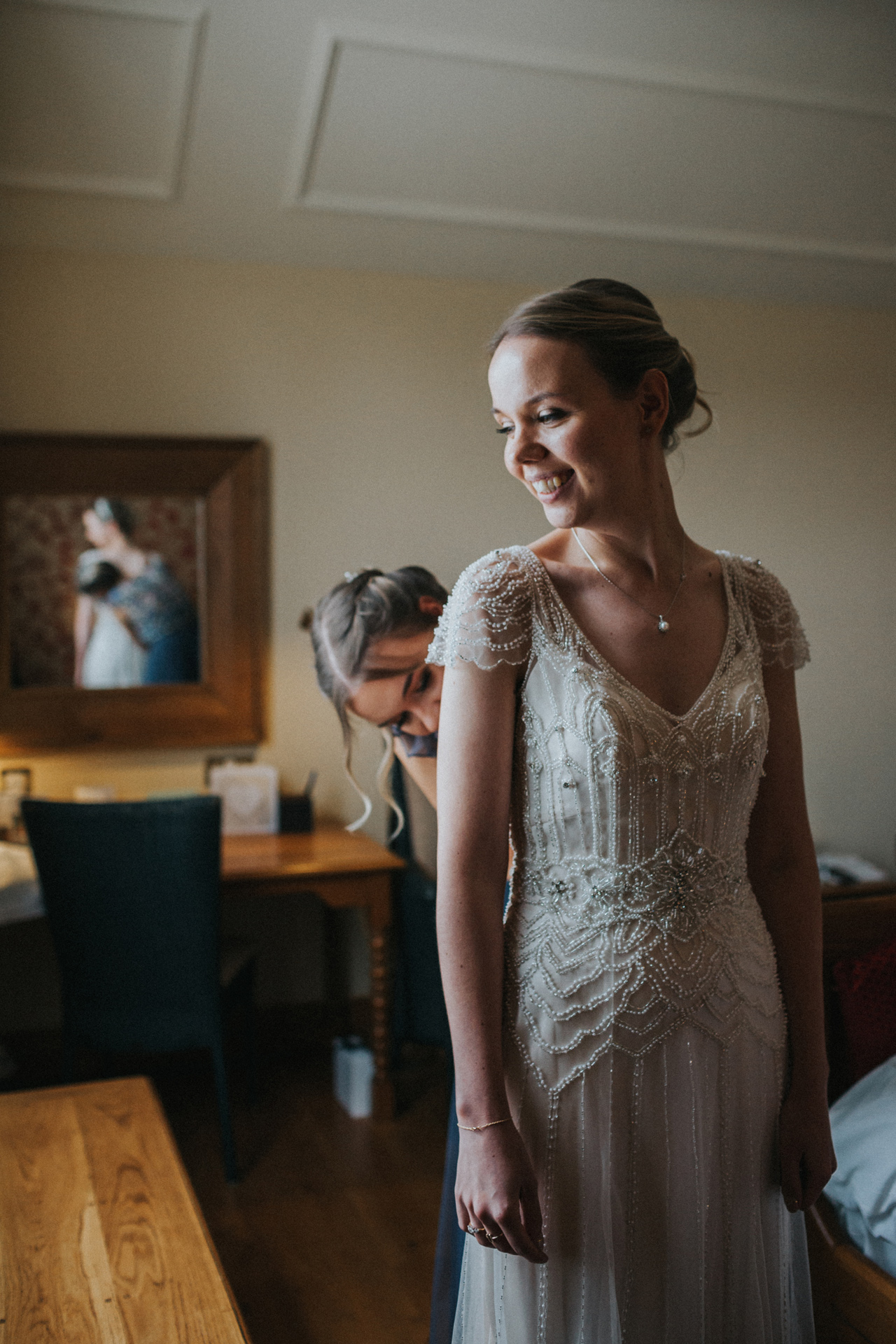 Bride stands smiling while wearing her wedding dress.