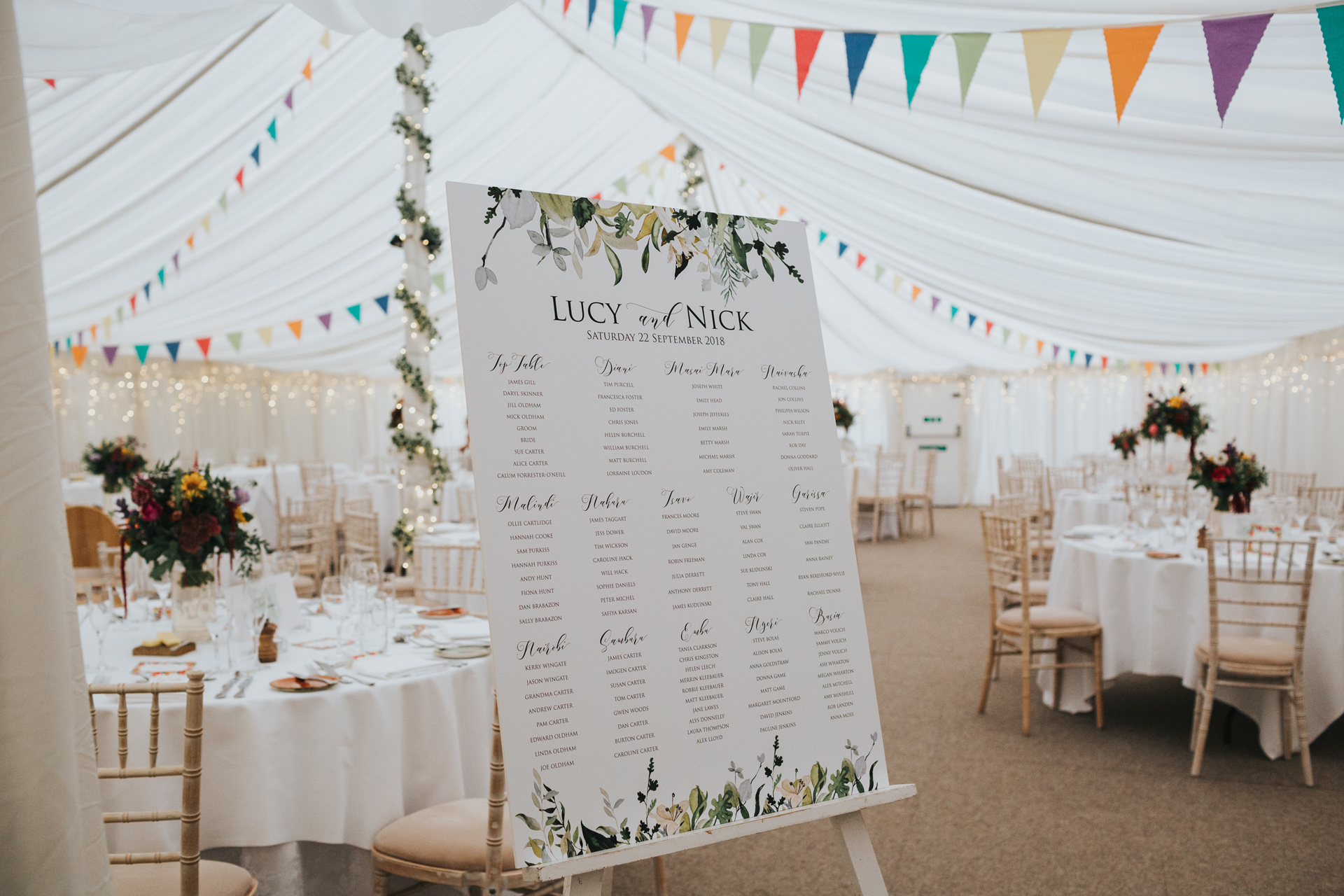 Table plan in marquee full of colourful flowers and bunting at Goldstone Hall.