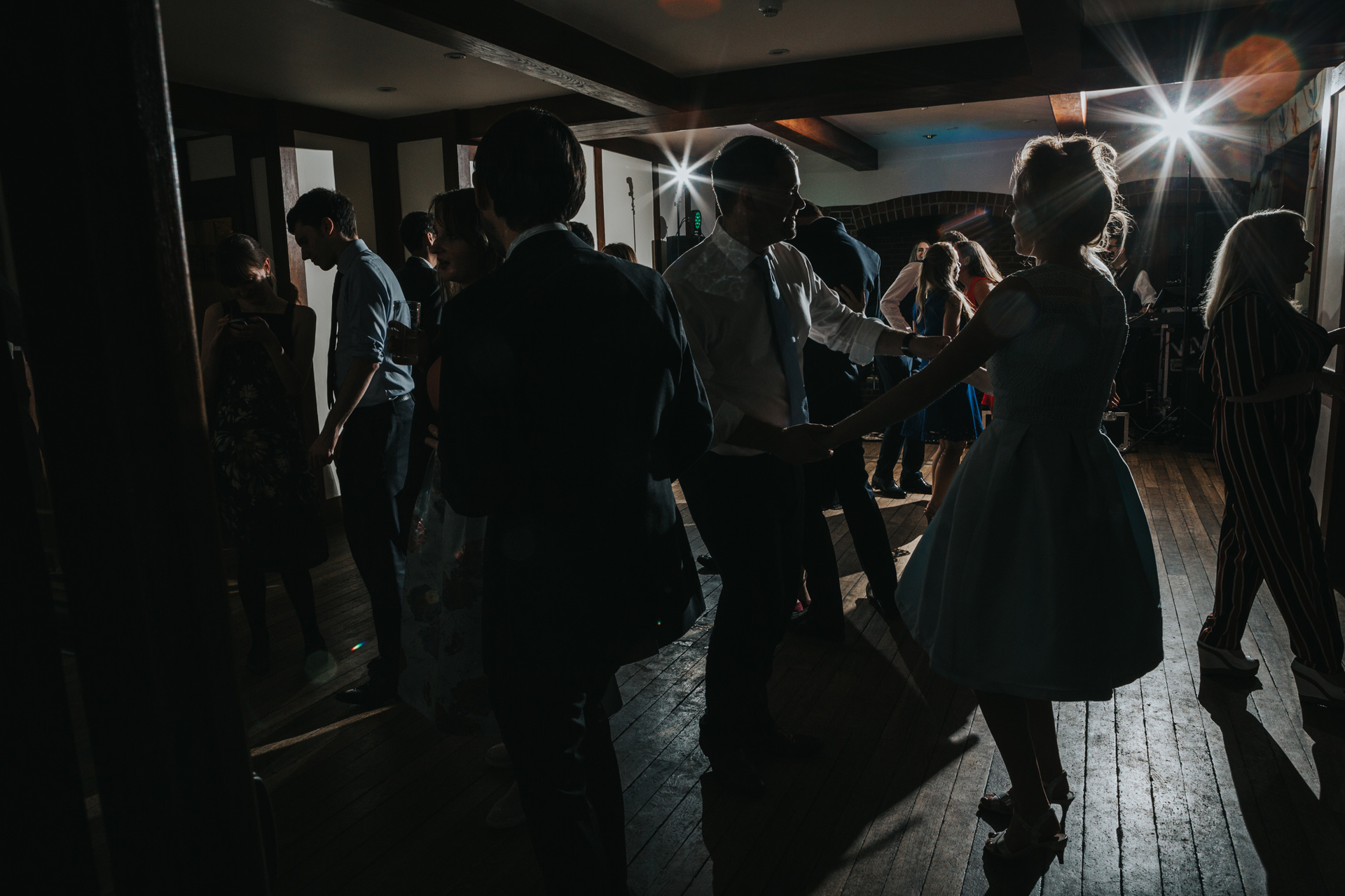 Couple are silhouetted while they dance together, female guests wears a 50's type dress.