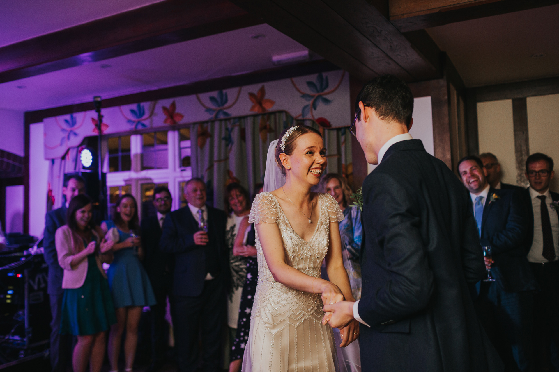 Bride laughs while dancing with her new husband.