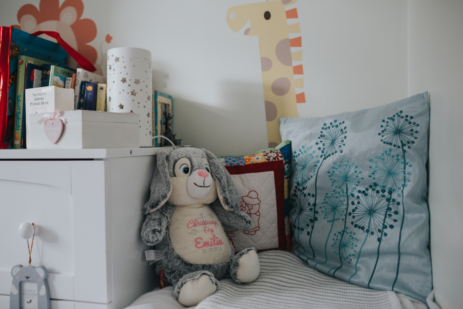 A fluffy toy bunny rabbit sits alongside other toys in the child's bedroom.