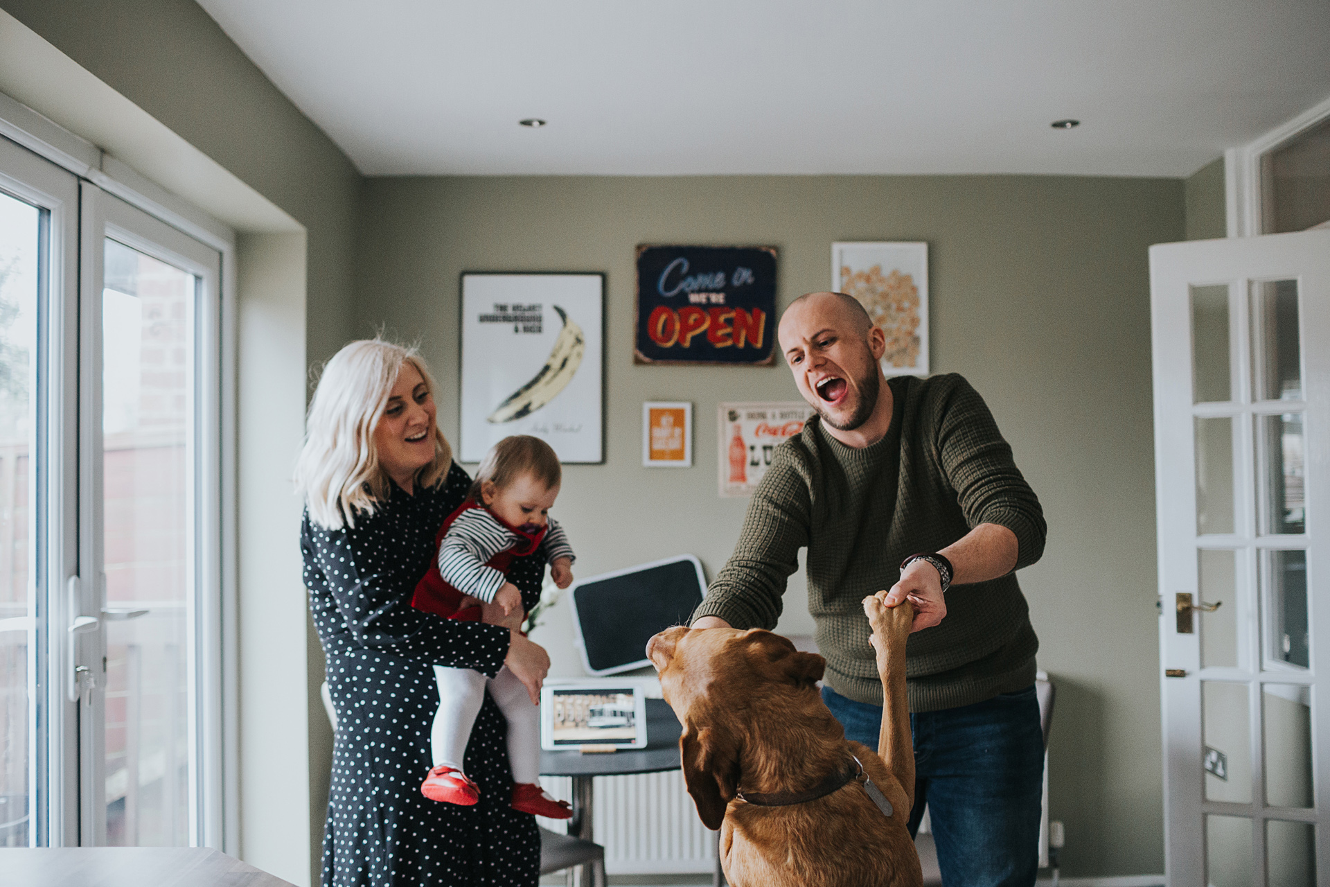 Family have a dance with the dog in the kitchen.