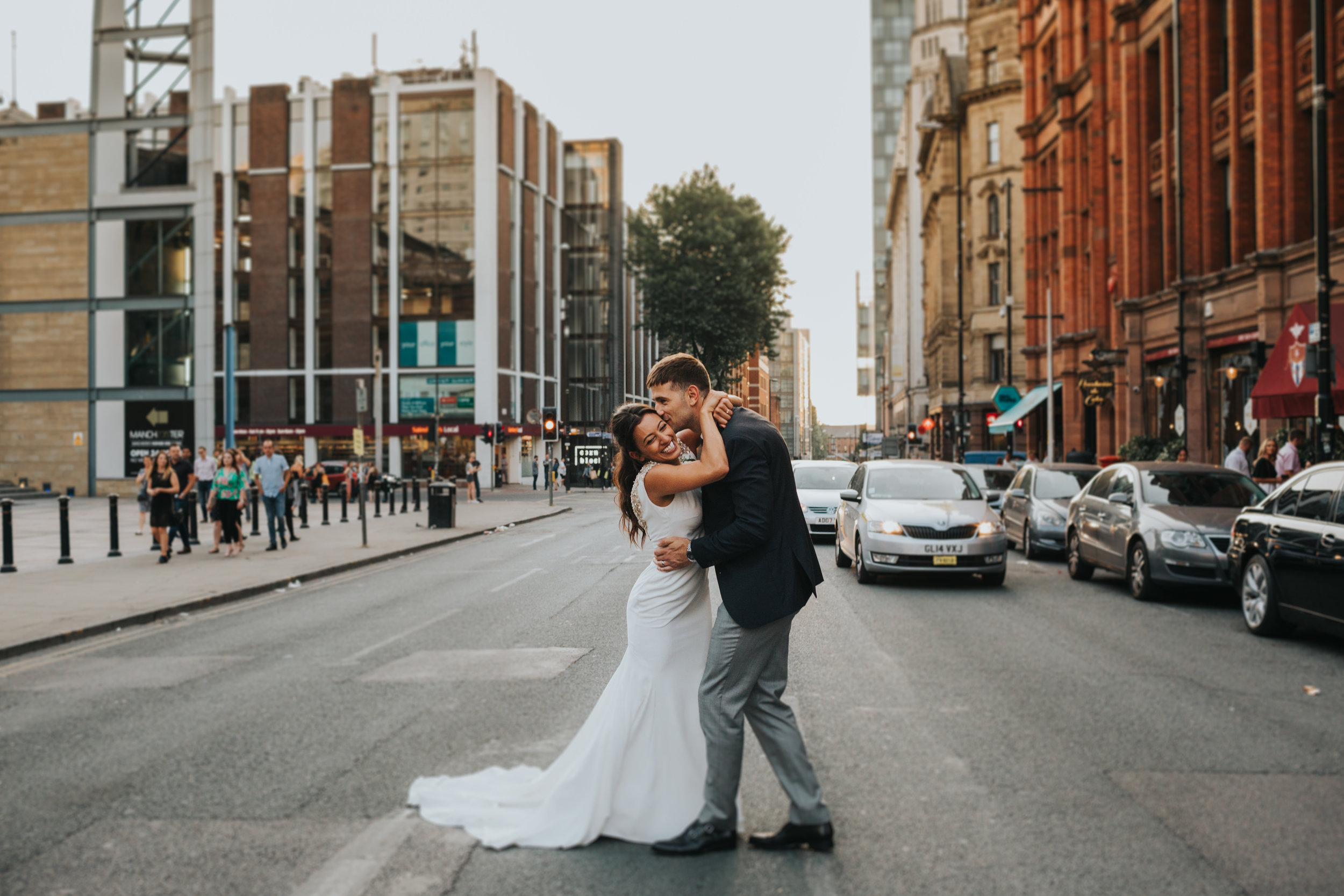 Couple kiss in the street outside Albert Hall Manchester on their wedding day.