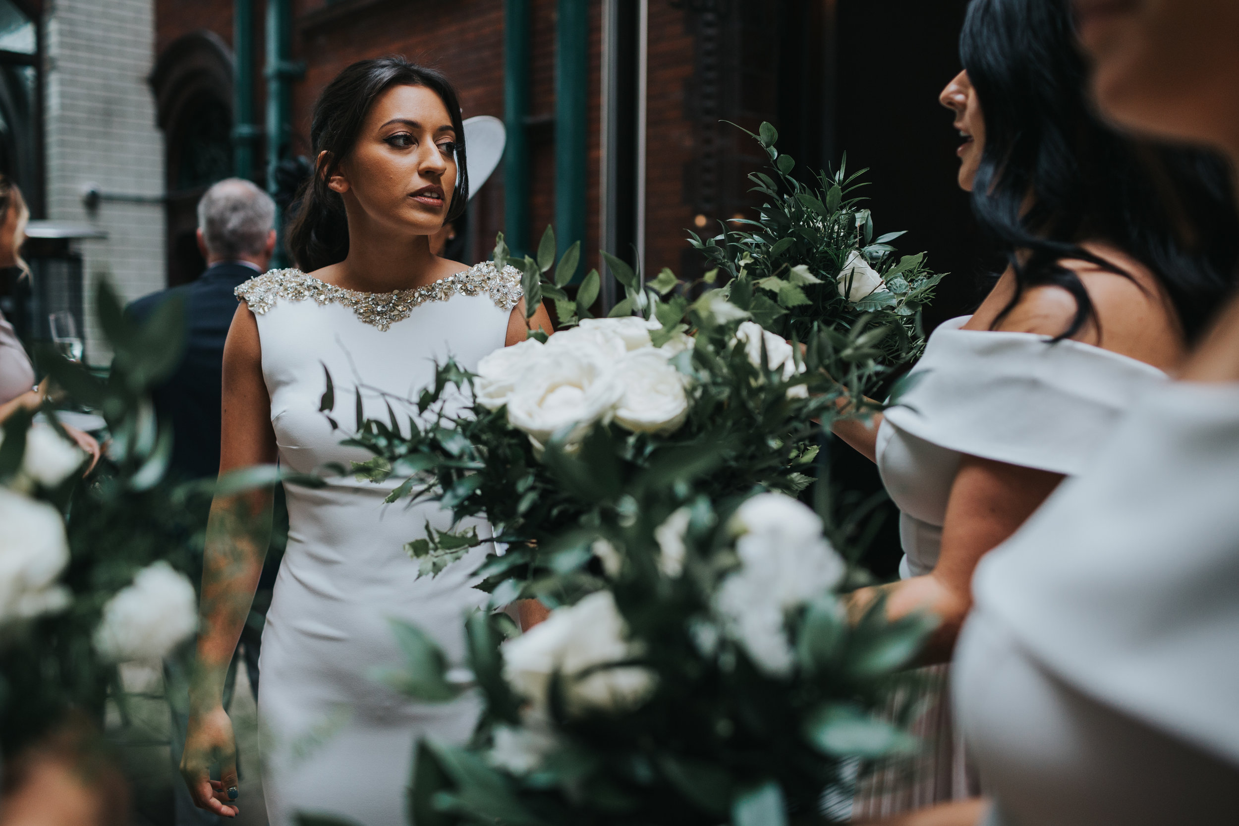 The bride leaves her hotel to get to the church, surrounded by her bridesmaids beautiful white and green bouquets.