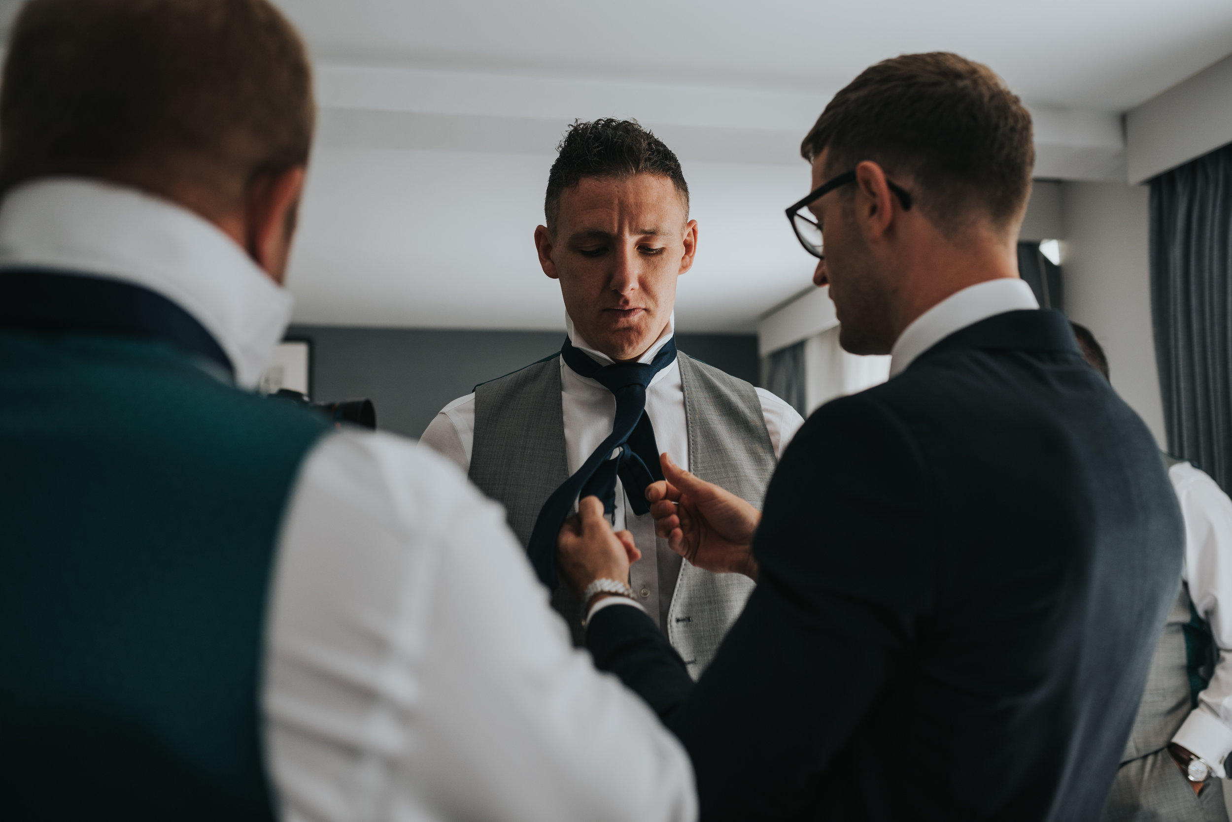 The groom fixes one of his groomsmen's ties.