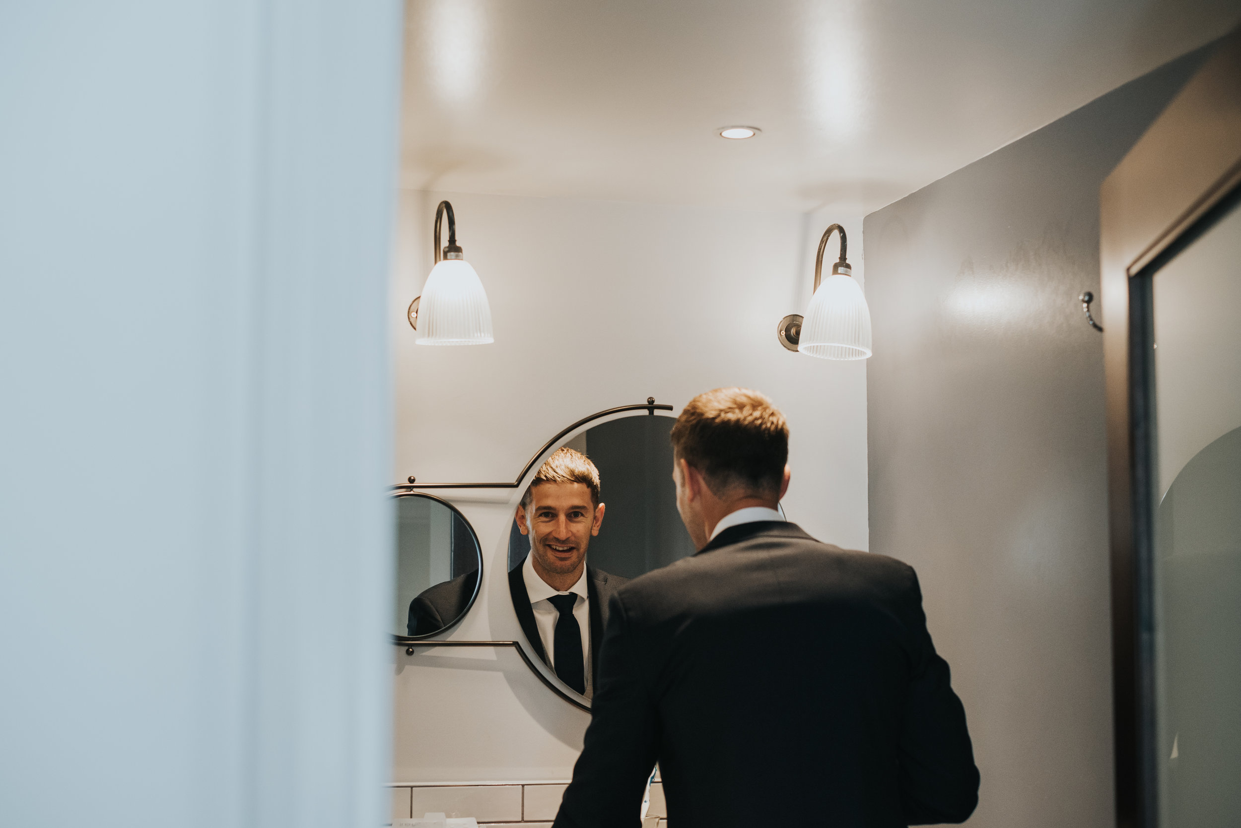 The groom catches the photographer snapping him in the bathroom mirror.