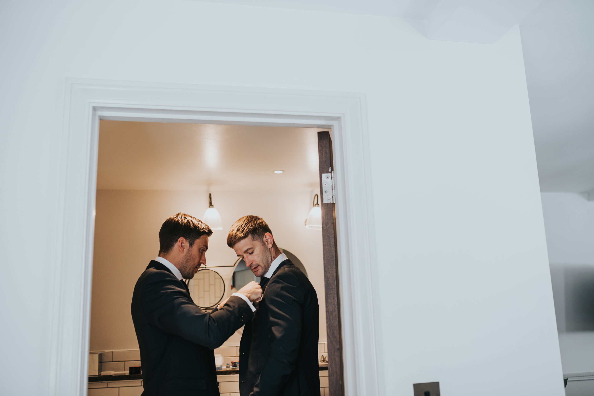 The groom has his groomsman fix his suit for him.