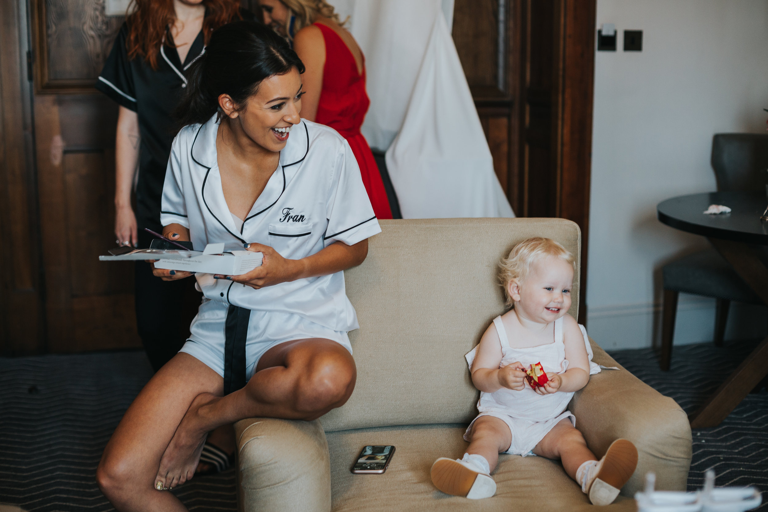 Bride sits with her niece and laughs.