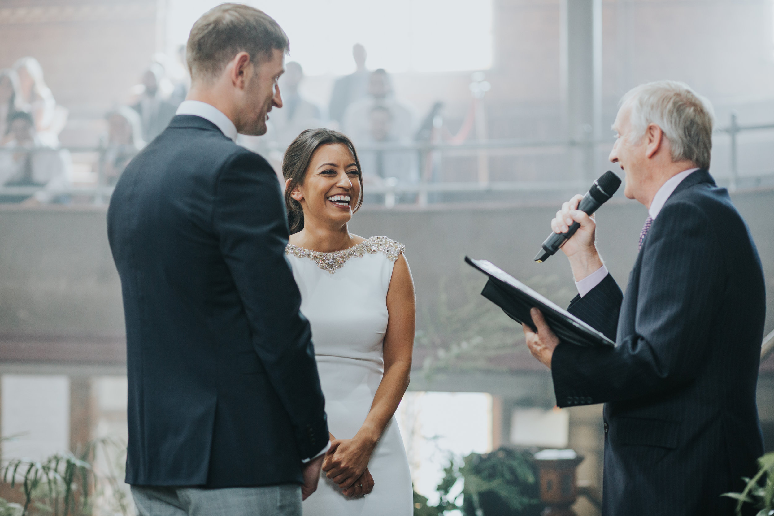 Bride laughing as the officiant makes a joke.
