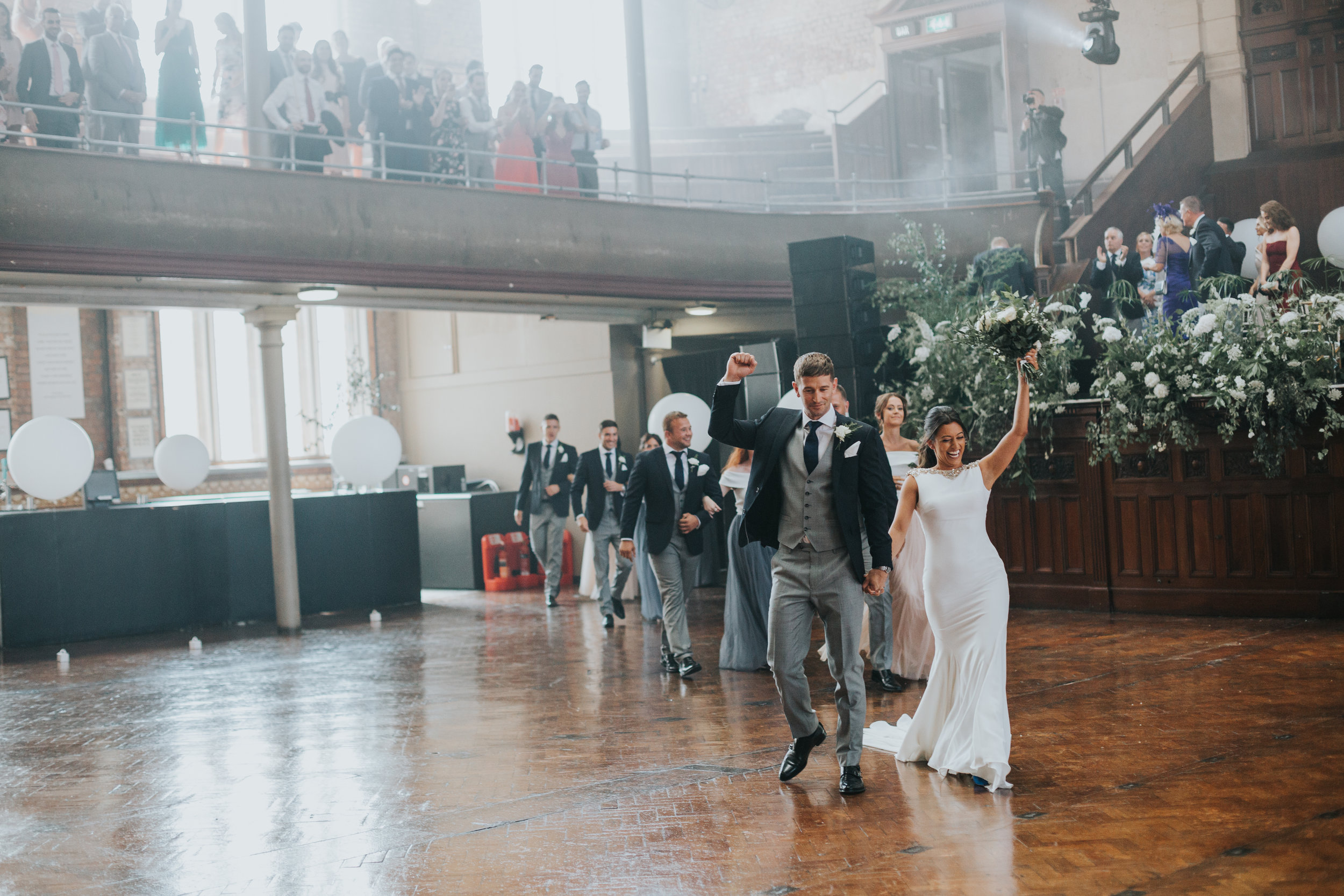 Bride and groom raise hands in the air as they make their way across the main hall floor to an audience of cheering guests!