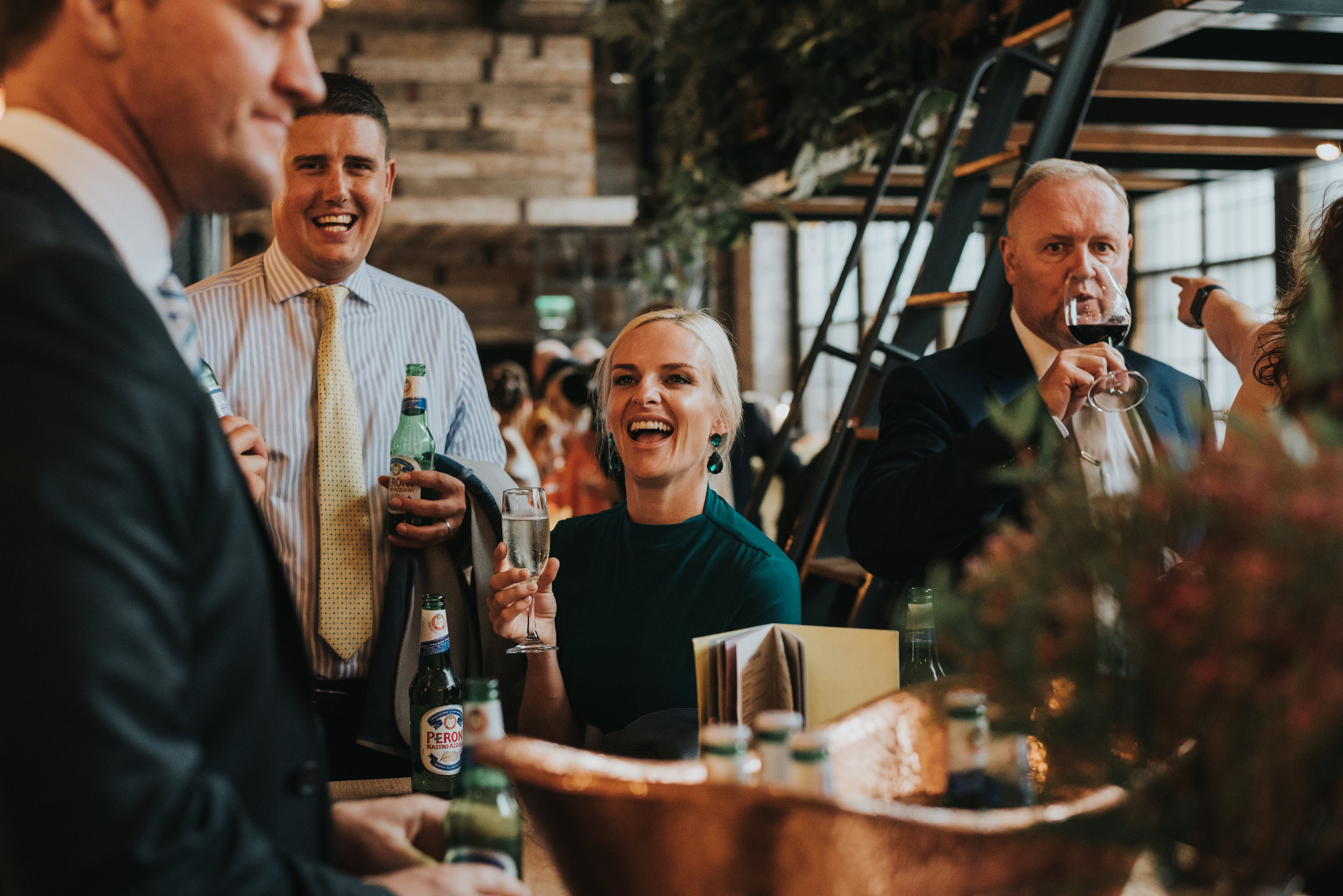 Wedding guests have a drink and laugh together in Albert Schloss.