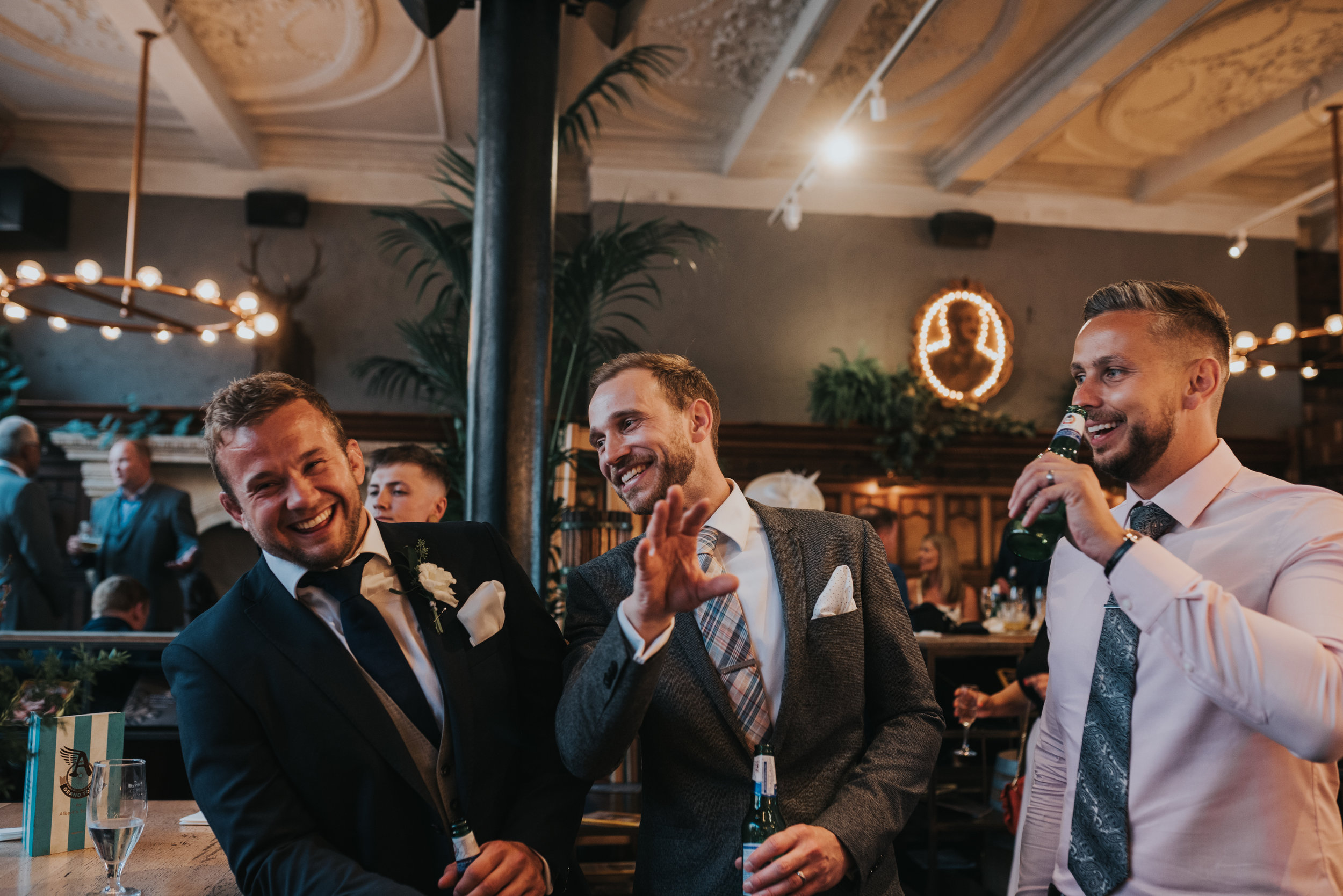 Three male wedding guests laugh together.