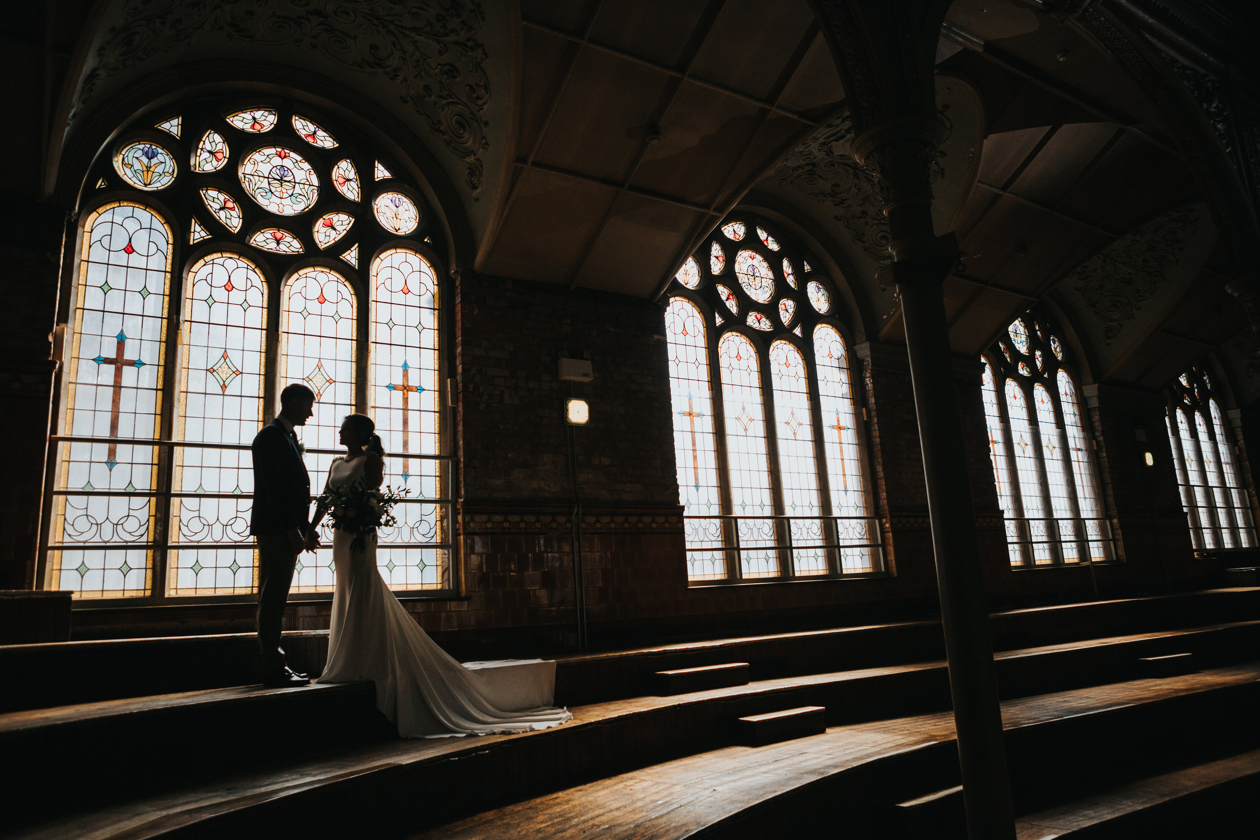 The couple stand holding hands in front of a huge stain glass window.