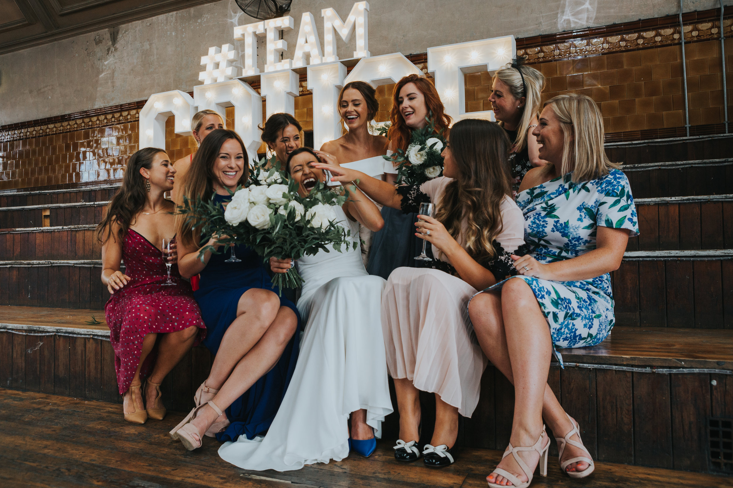 Bride sits in the middle of her female friends laughing as they try and poke her in the face, huge TEAM CRUSE sign behind them.