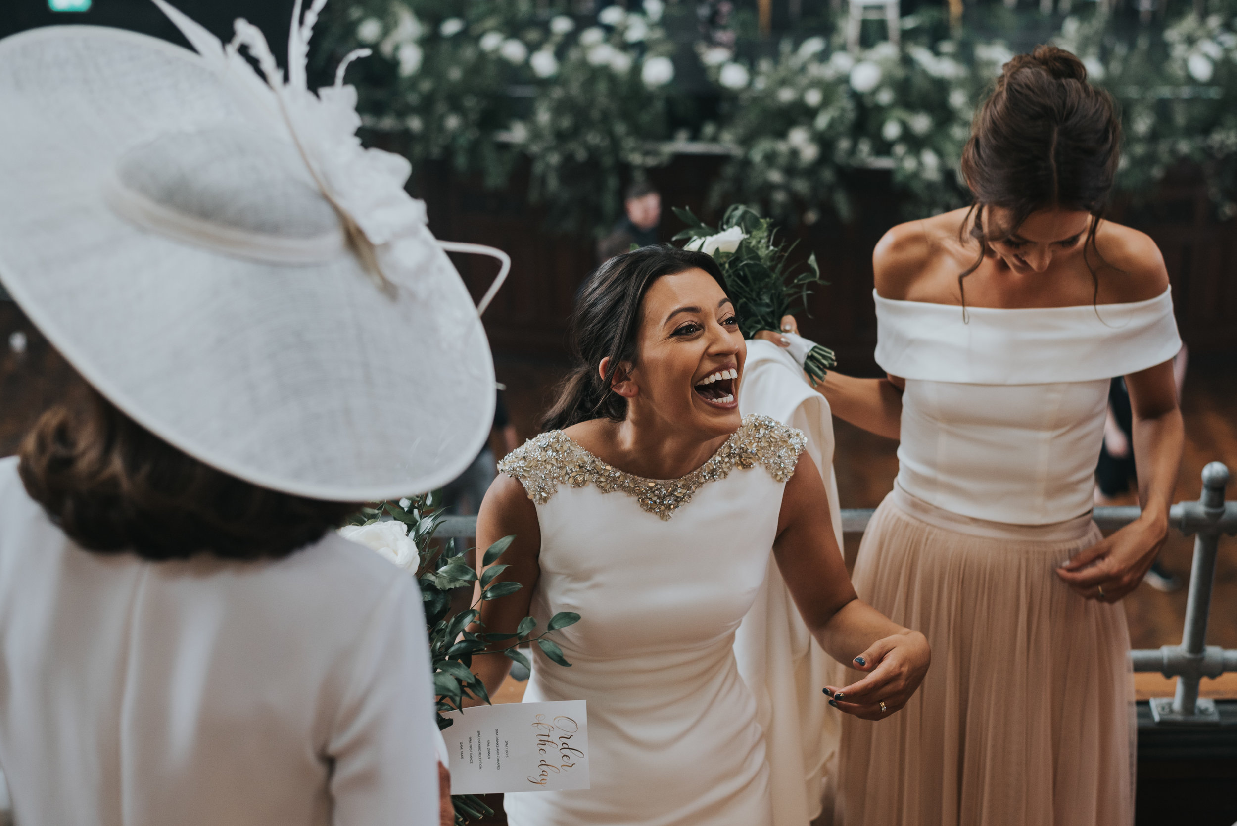 Bride laughing with mother of the bride and her bridesmaid.