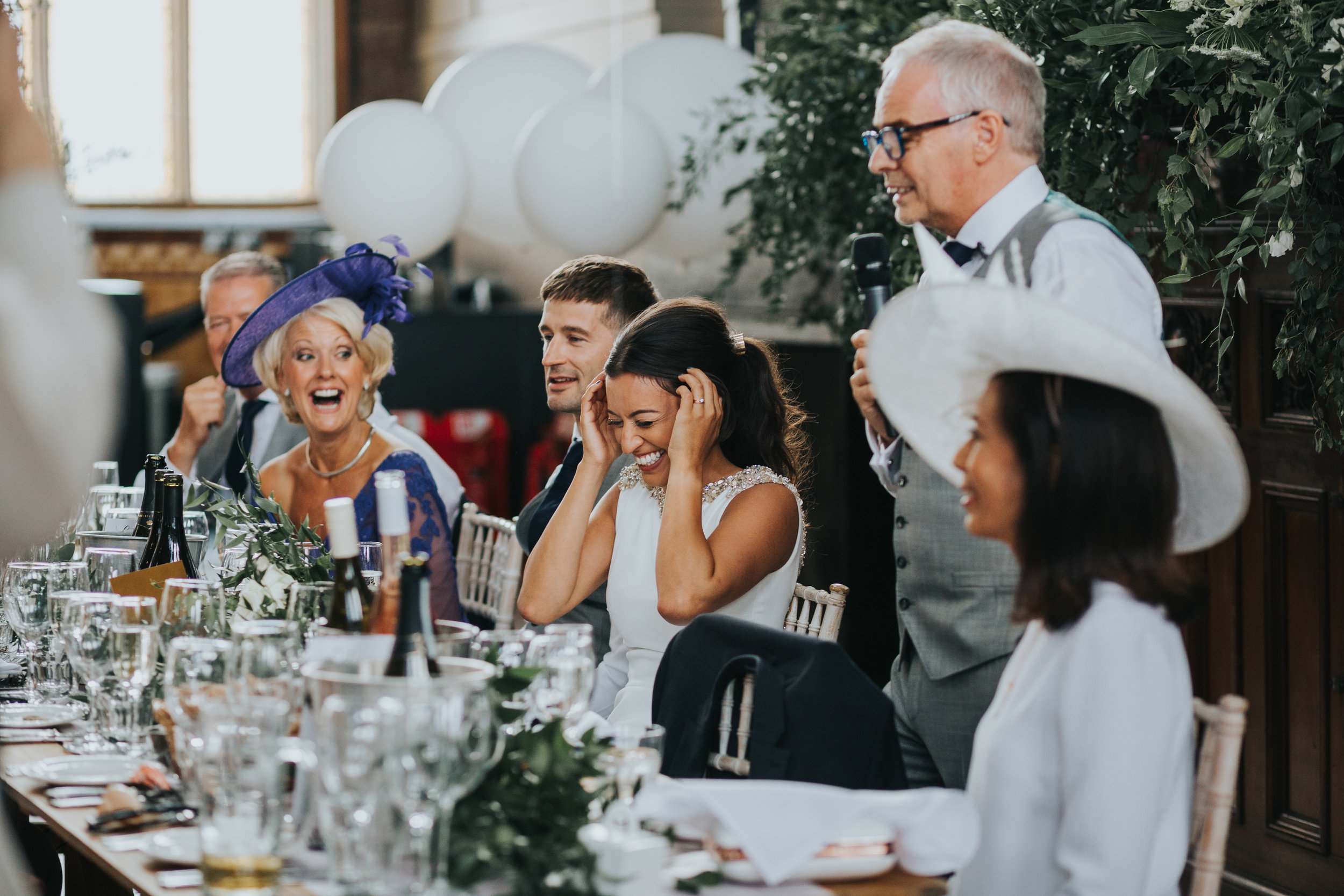 Bride laughs while listening to fathers speech.