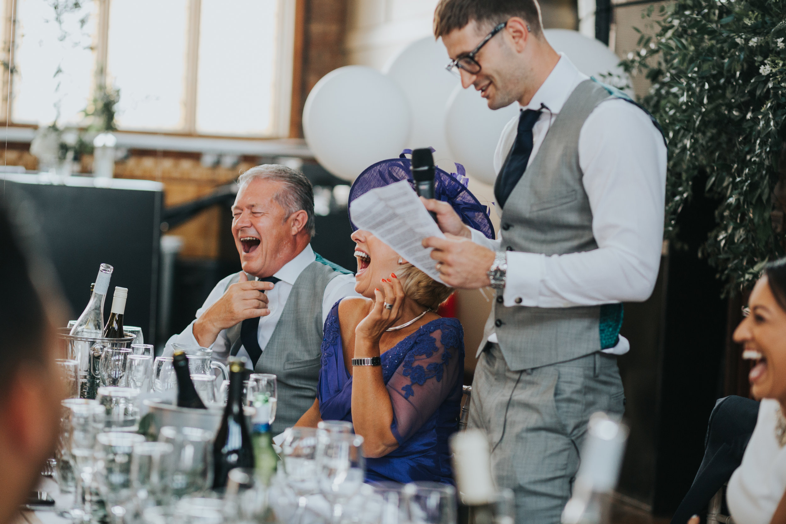 Groom makes his speech as his parents laugh.