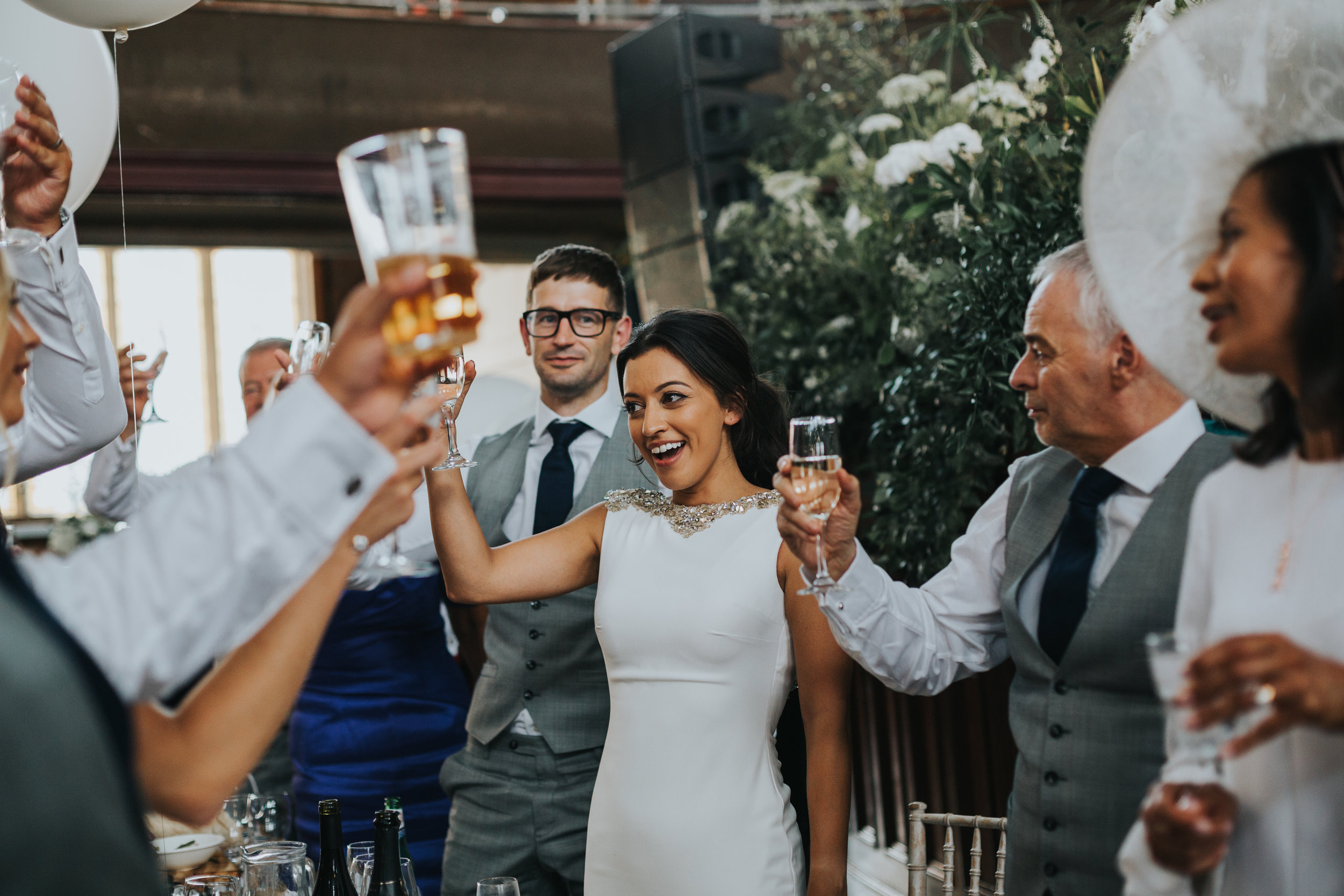 Bride and groom raise their glasses to cheers the best mans speech.
