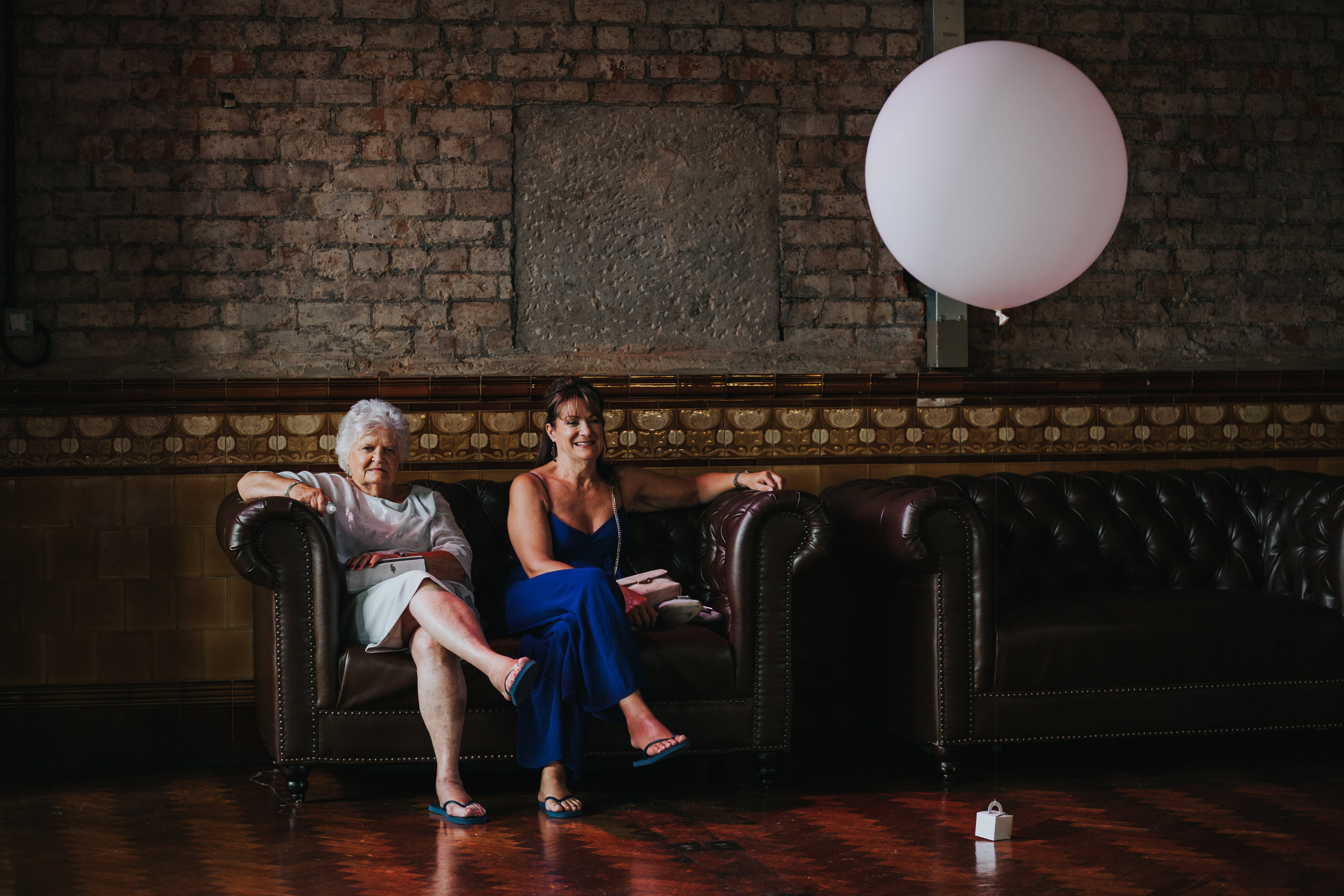 Two guests take refuge on a sofa next to a big white balloon.