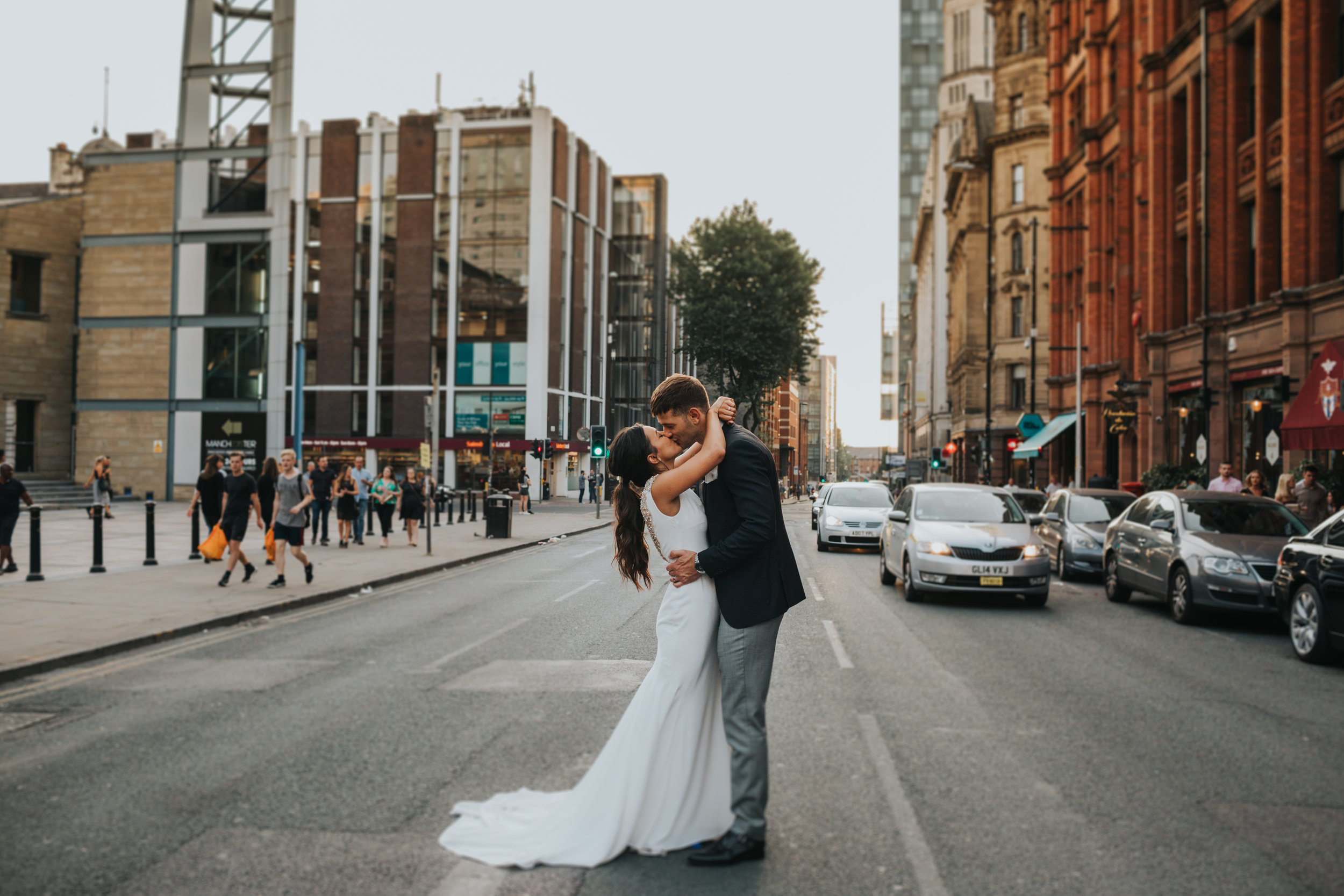 Bride and groom kiss in the middle of the road outside the Albert hall, Manchester.
