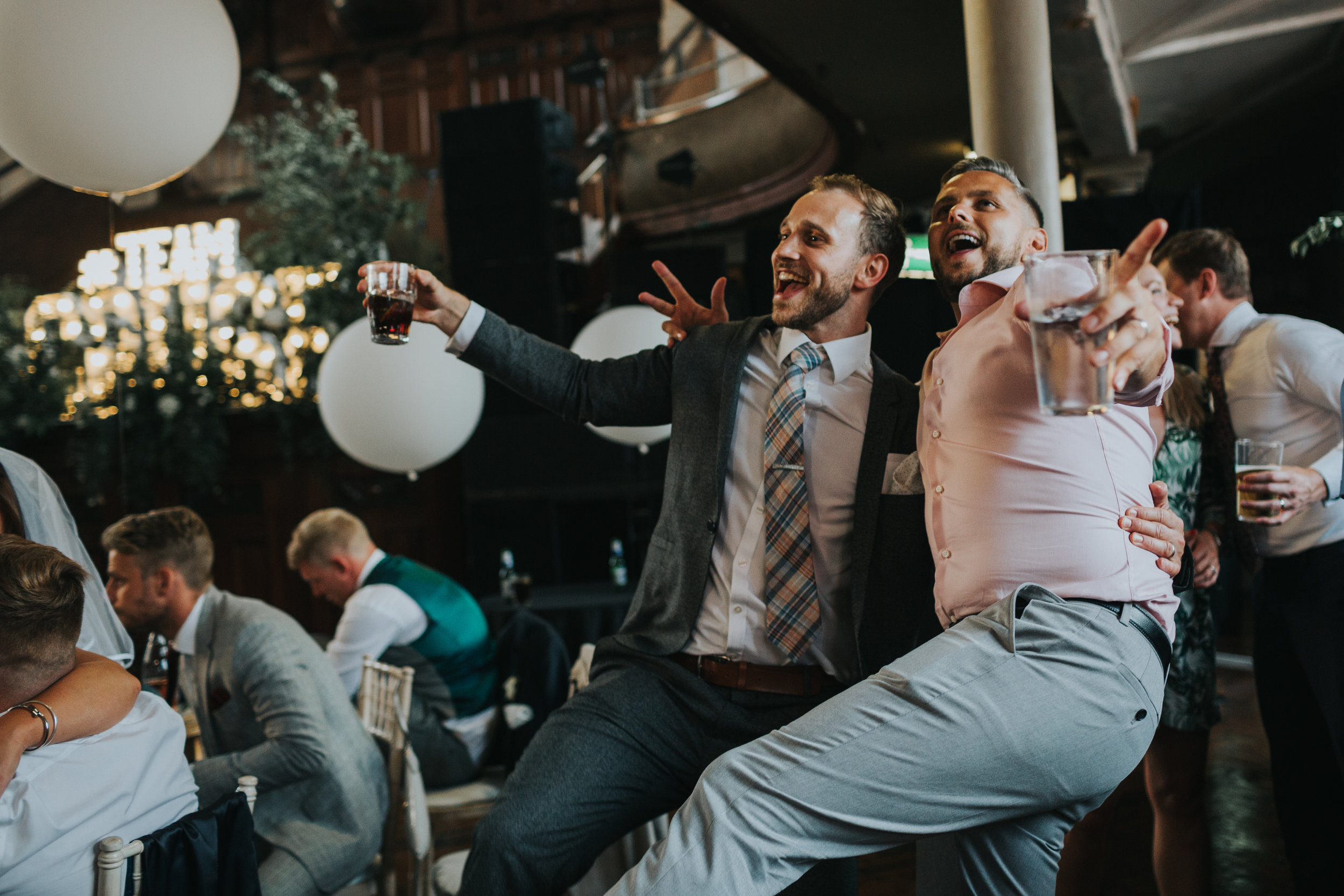 Two male wedding  guests dancing with their legs in the air.