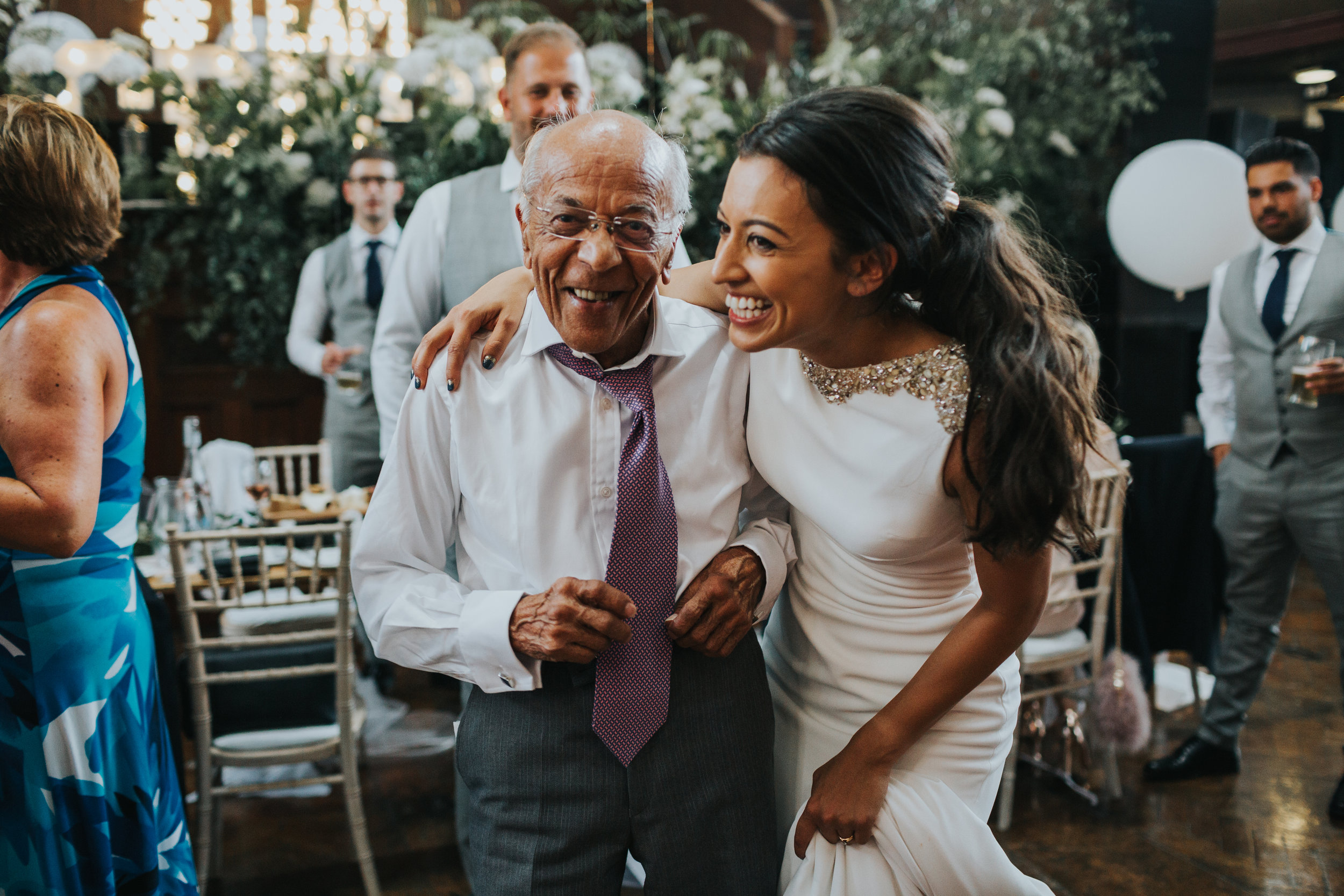 Bride and grandad laugh together at the Albert Hall Manchester.
