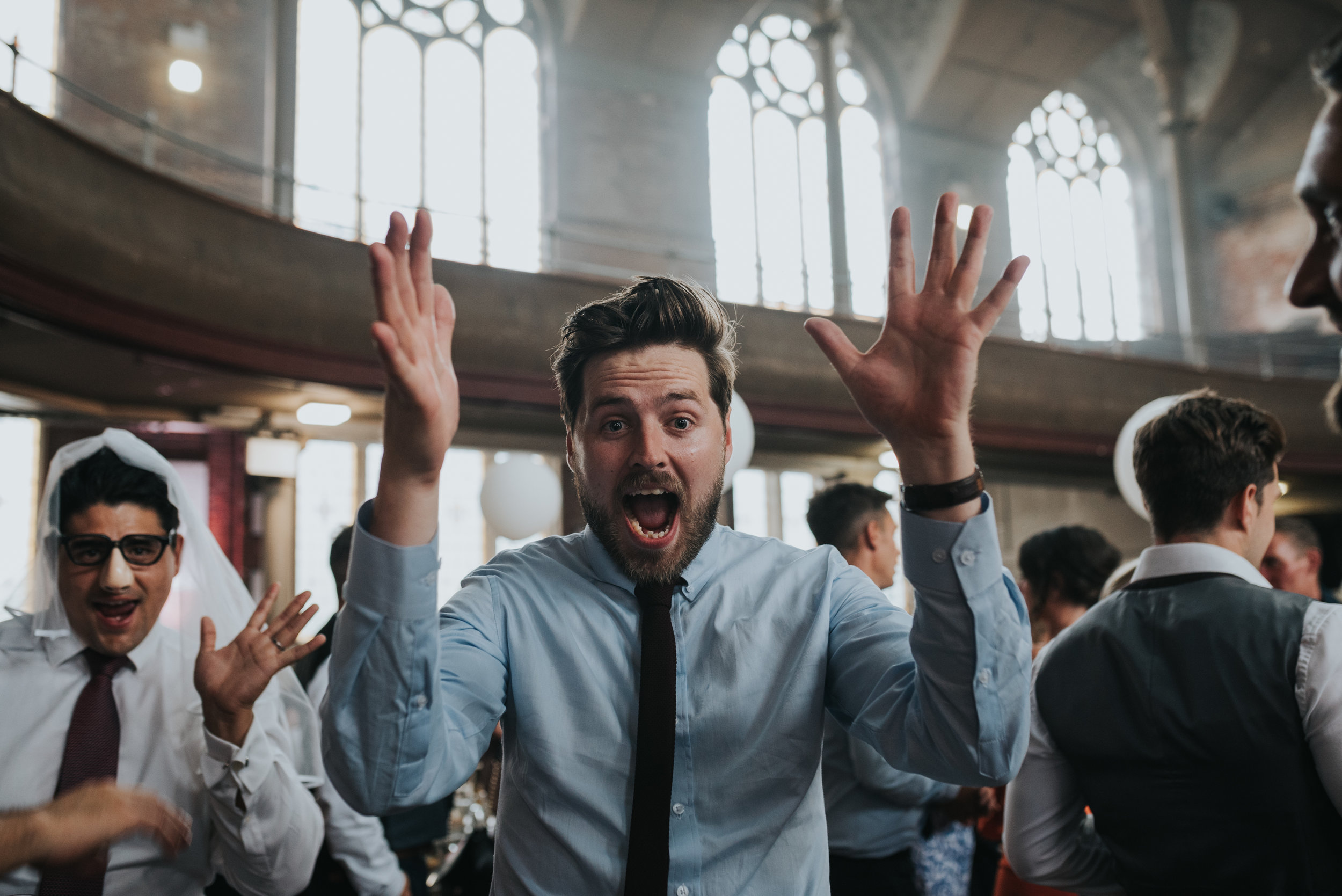 Wedding guest with shocked face and hands in the air.