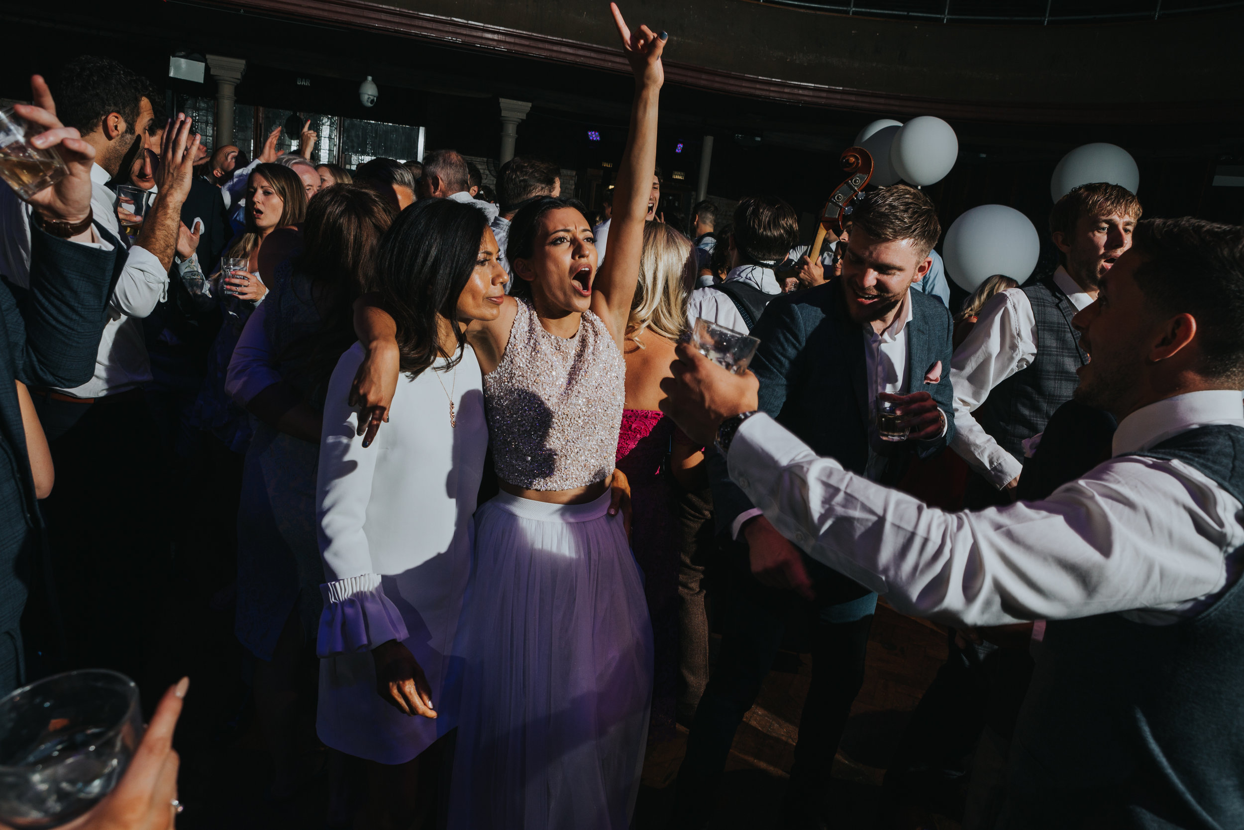 Bride raises her hand in the air singing to the music.