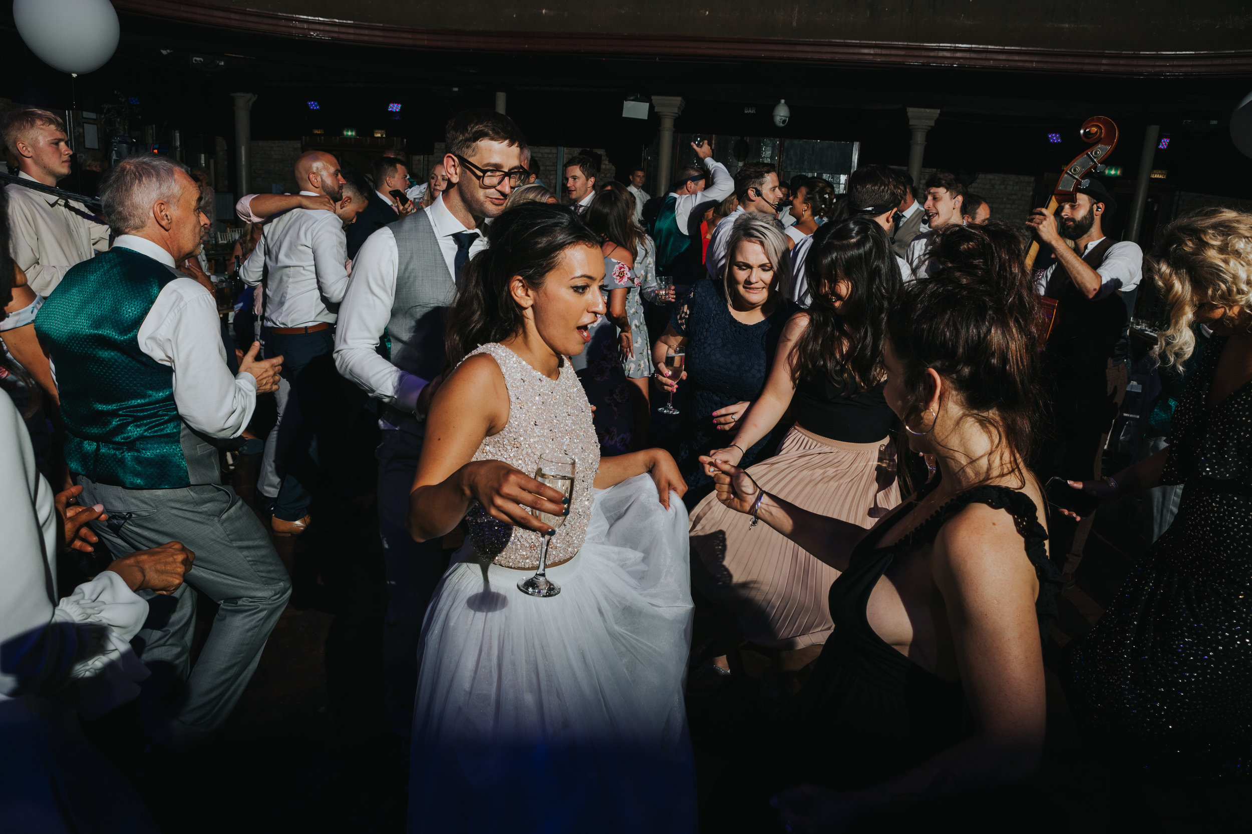 Bride dances in the middle of her friends swishing her skirt around.