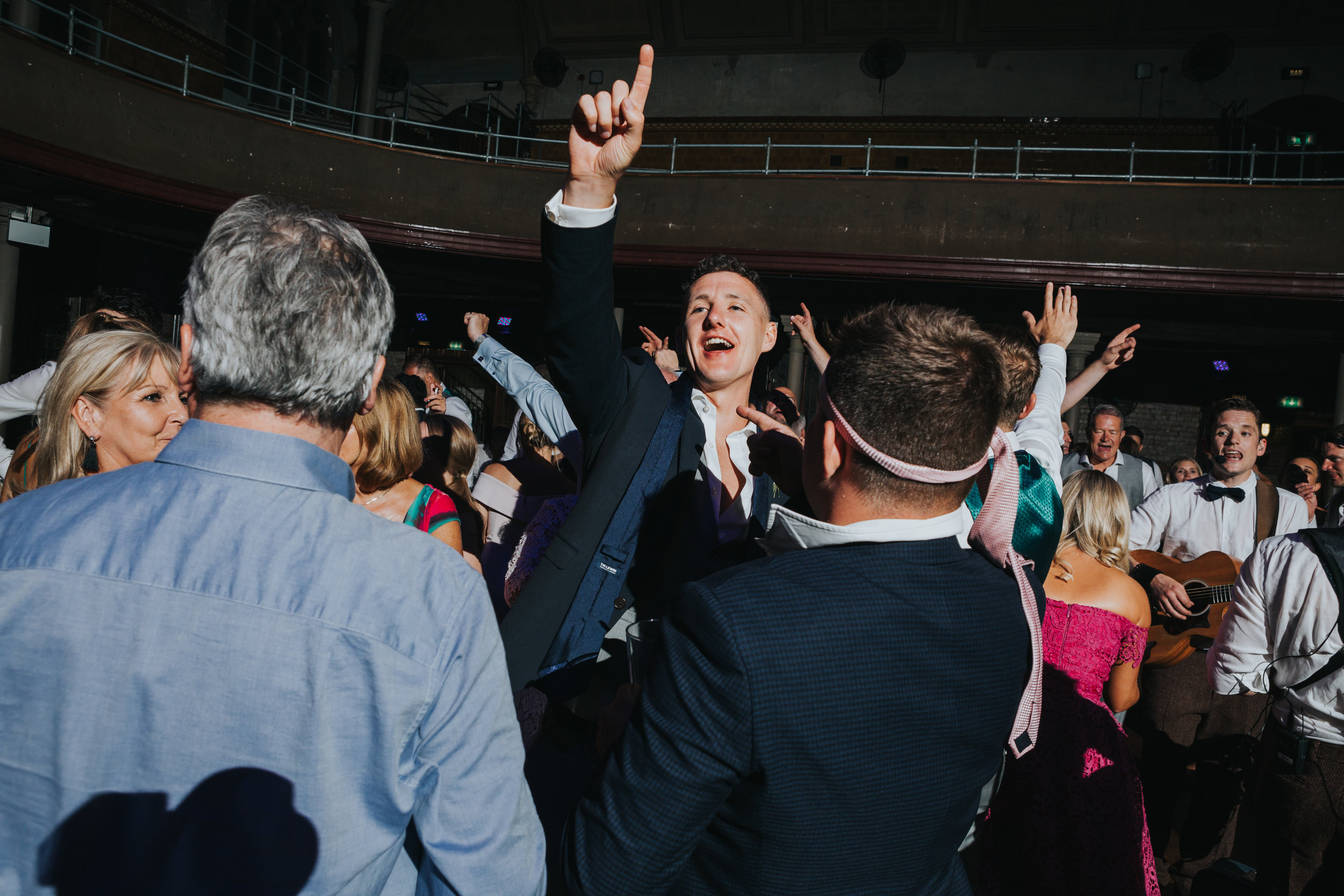 Male weddings guests dance with their ties tied around their heads, Rambo style.