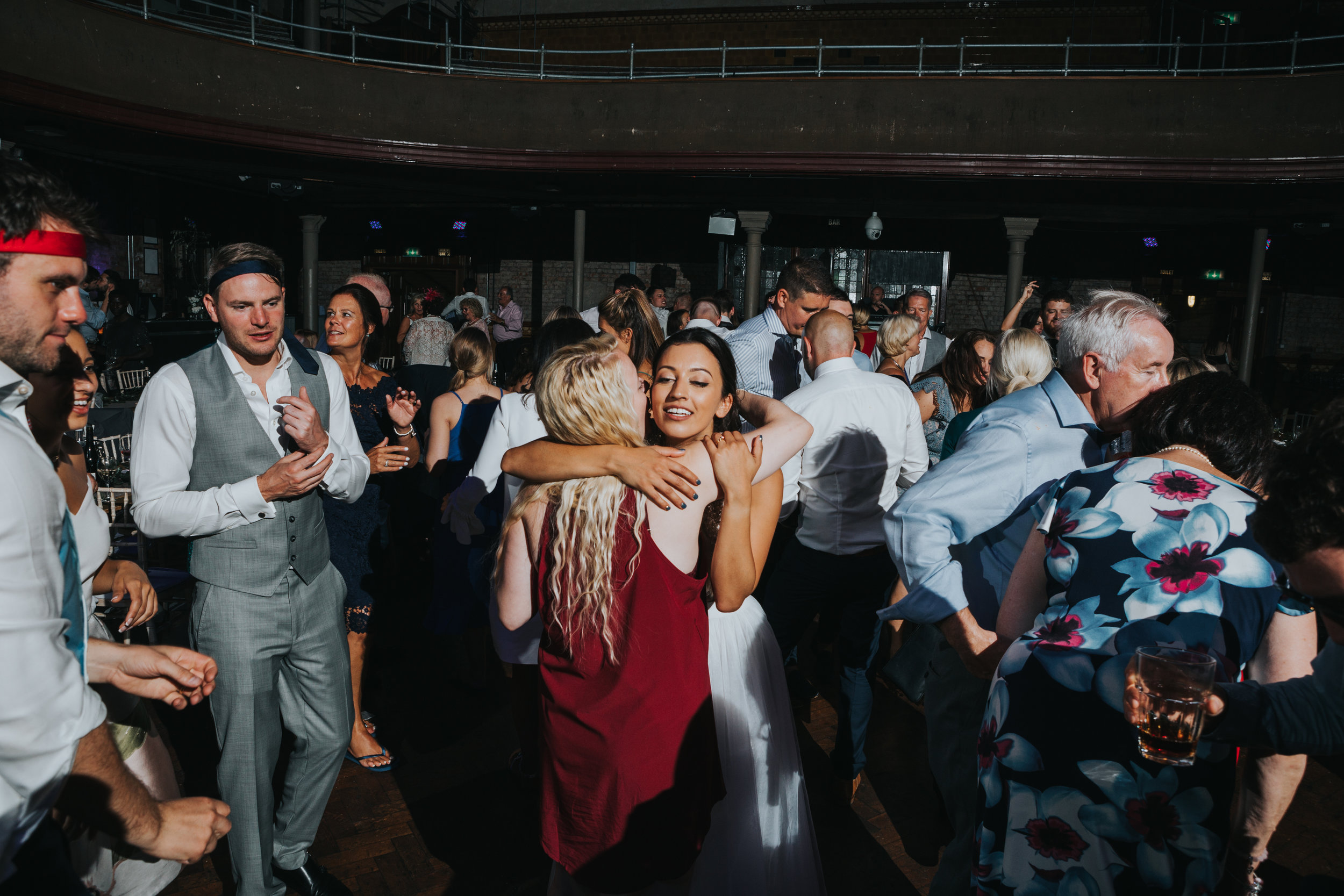 Bride hugs her friend on the dance floor.