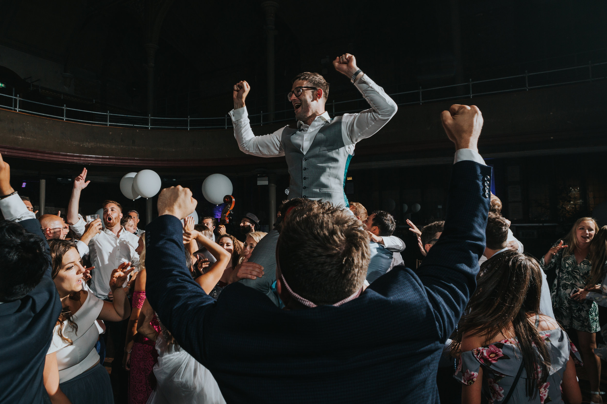 Groom sits on his friend shoulders with his hands in the air at The Albert Hall, Manchester.