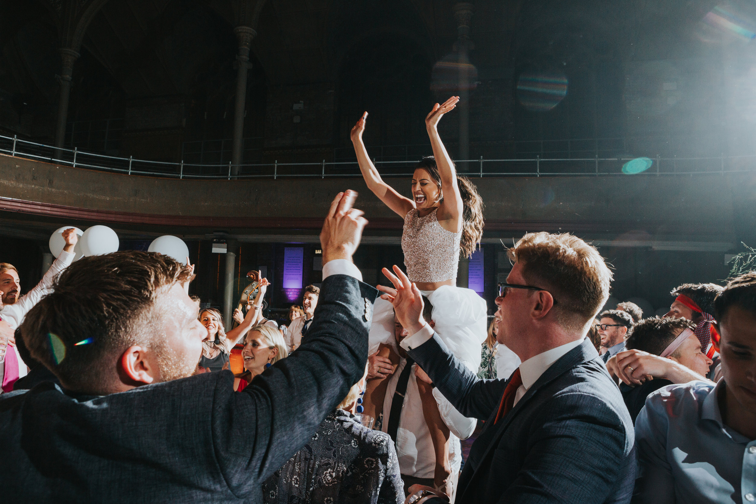 Bride sits on a guests shoulder, her hands in the air singing on her wedding day at The Albert Hall, Manchester.