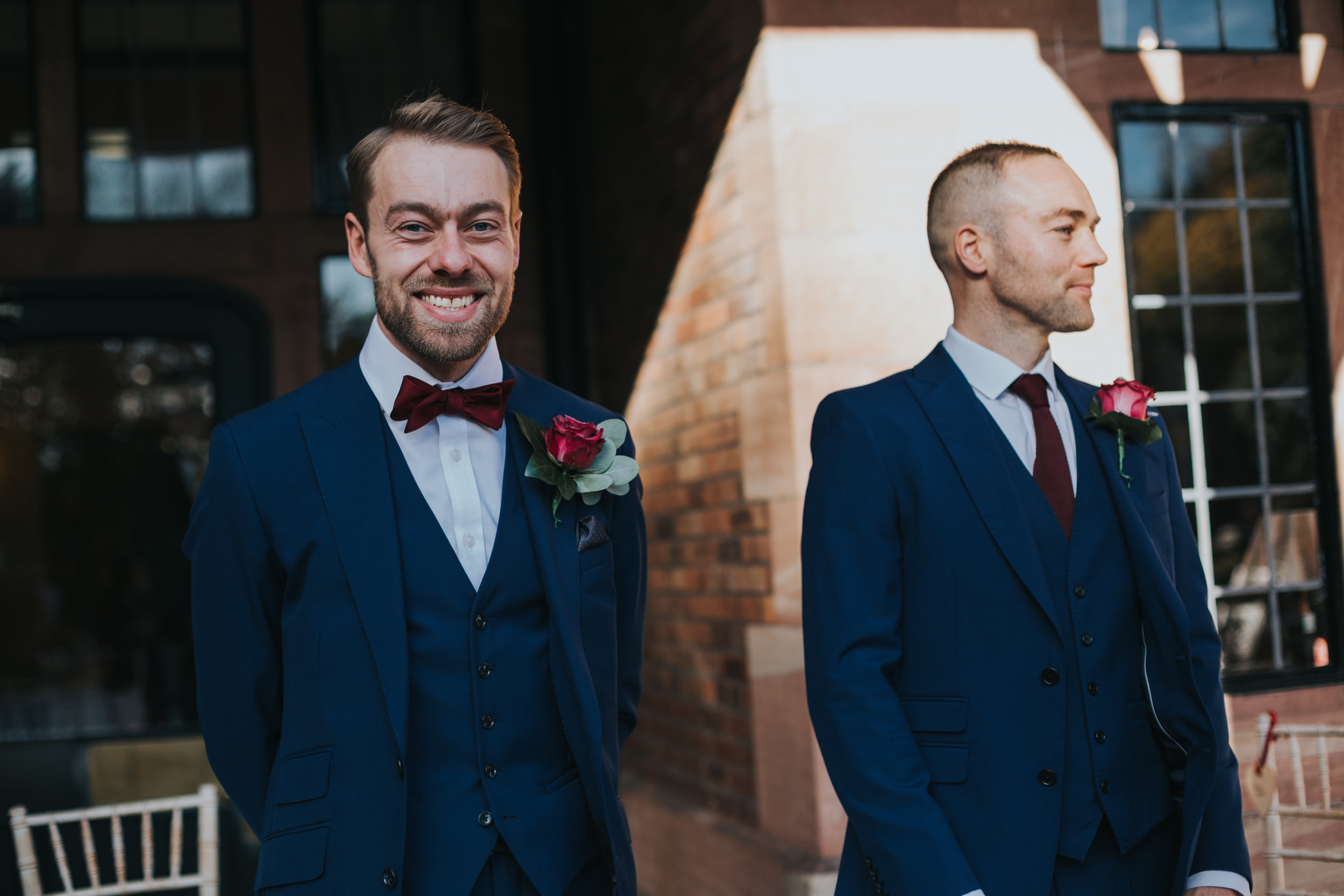 The groom and his best man stand smiling awaiting their guests at their outdoor ceremony at Inglewood Manor.