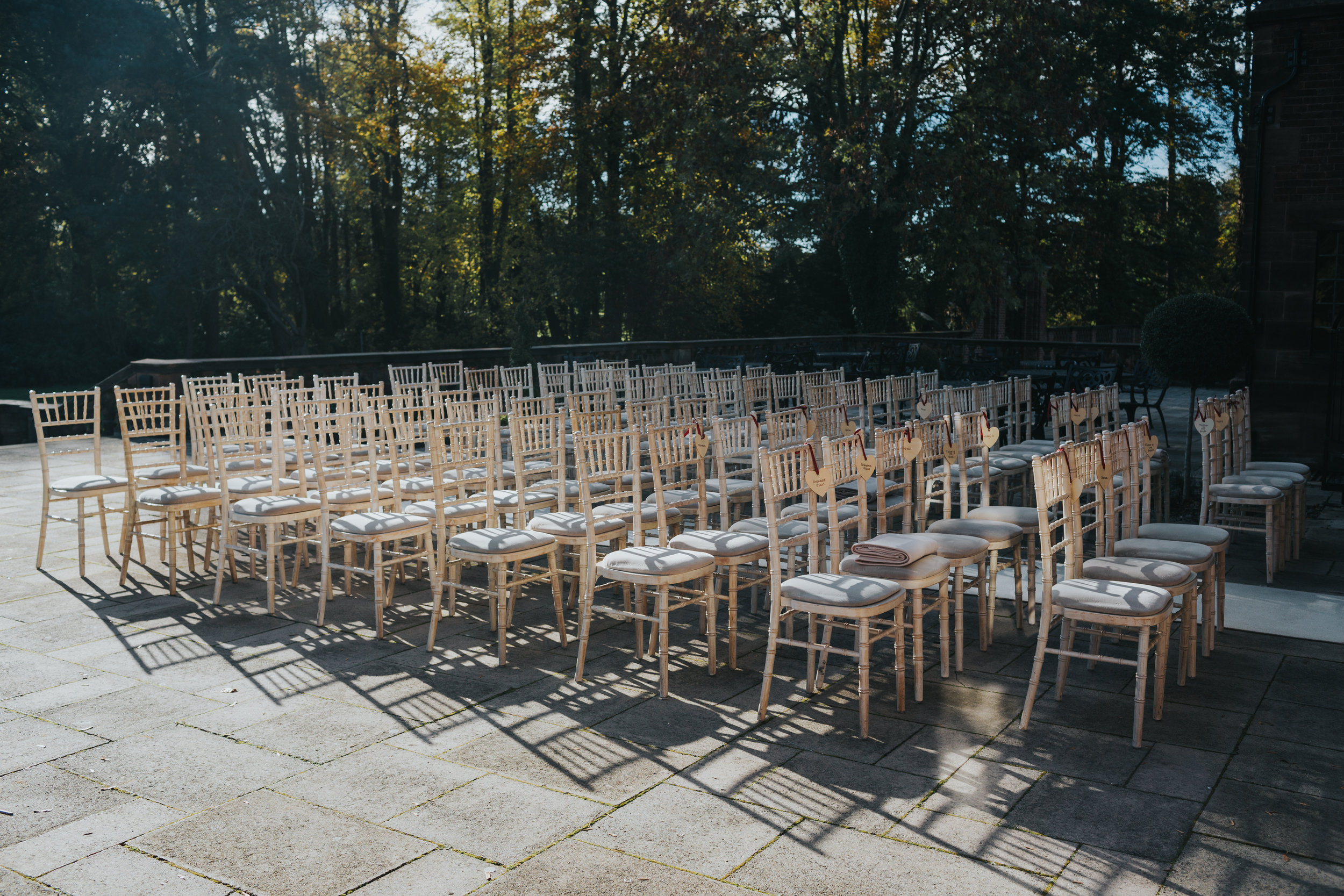 Empty cream wooden wedding chairs, sit empty in the sunlight casting shadows on patio awaiting the wedding guests.