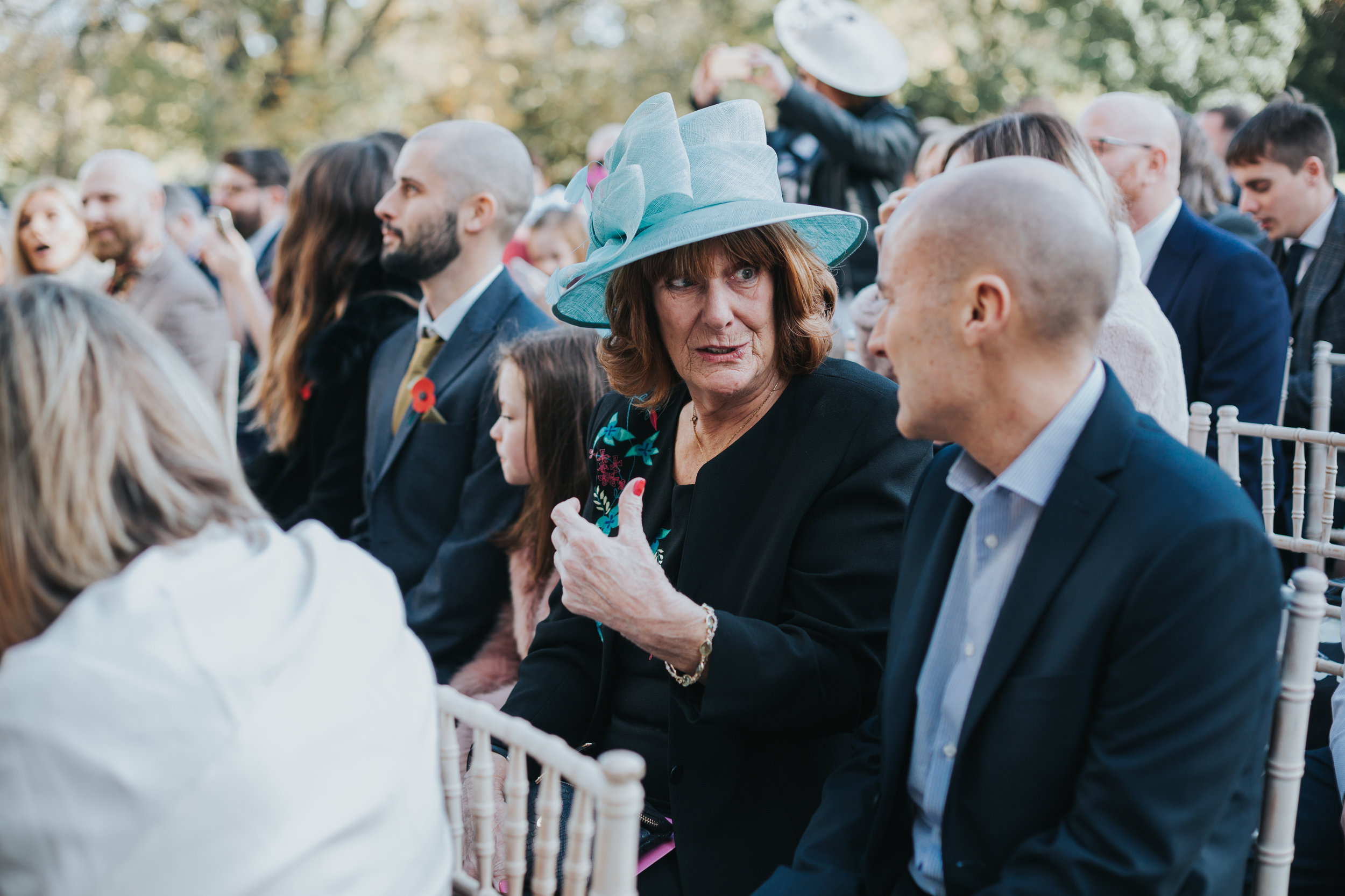 Wedding guests in blue hat chats with her friend.